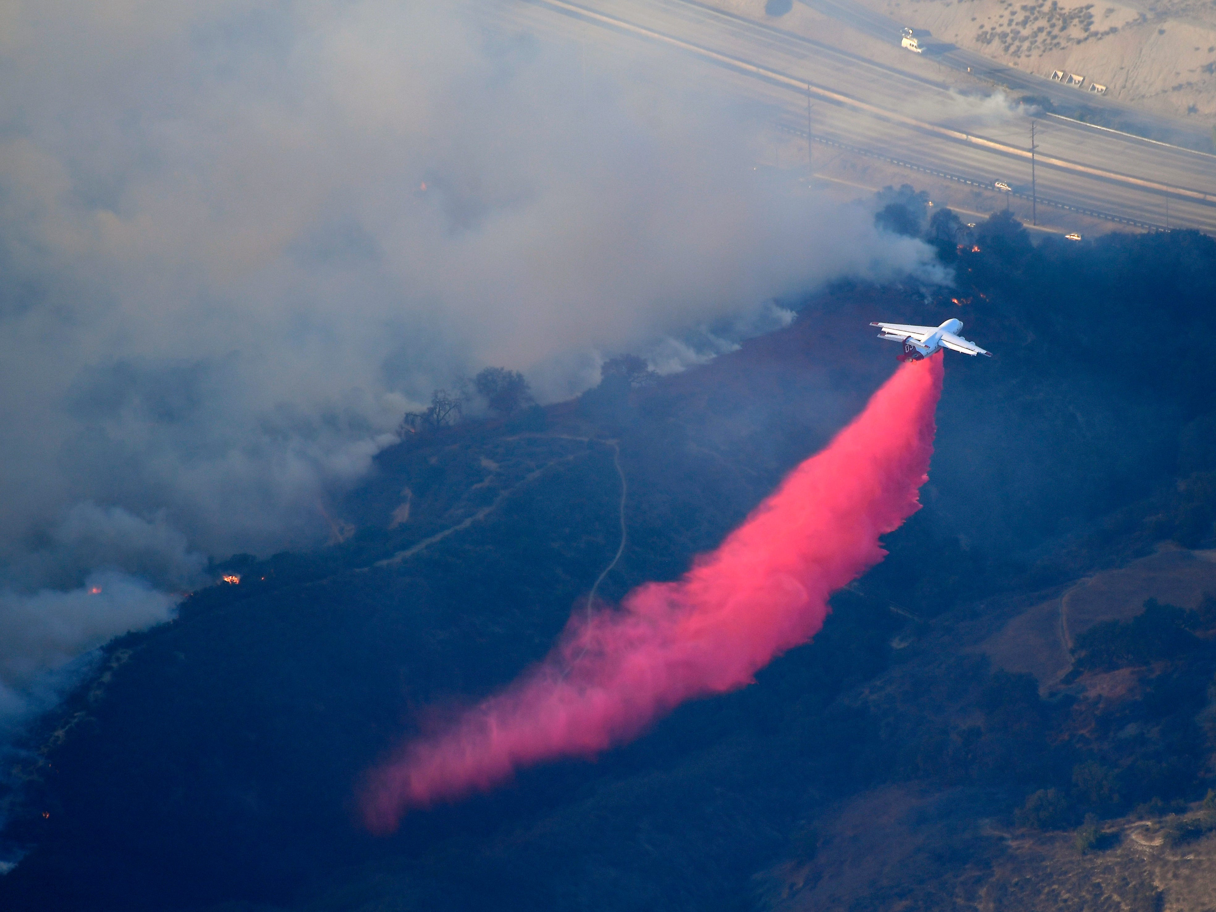 An air tanker drops flame retardant to protect homes as the Woolsey Fire burns Friday in Calabasas.