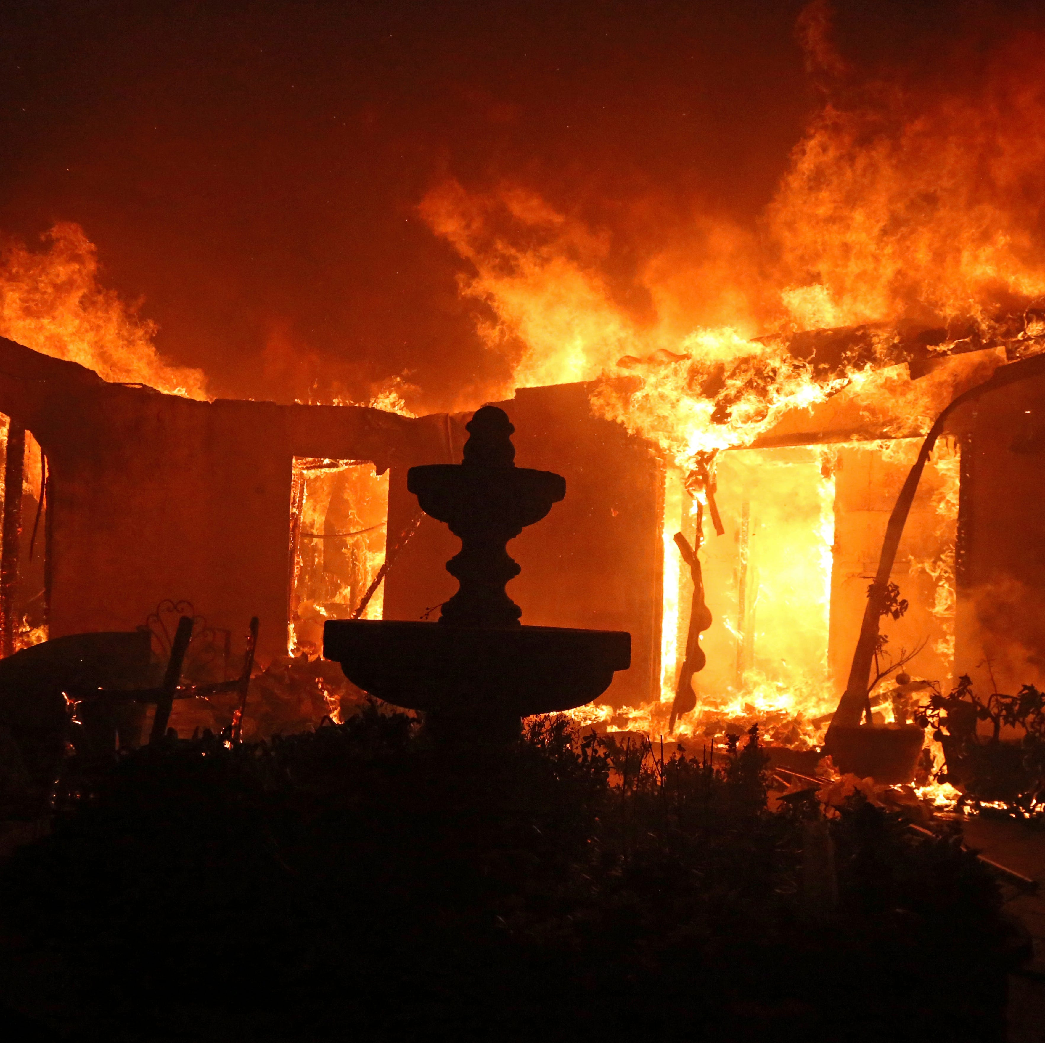 A Spanish-style home is consumed by flames from the Woolsey Fire on Dume Drive in Malibu on Friday.
