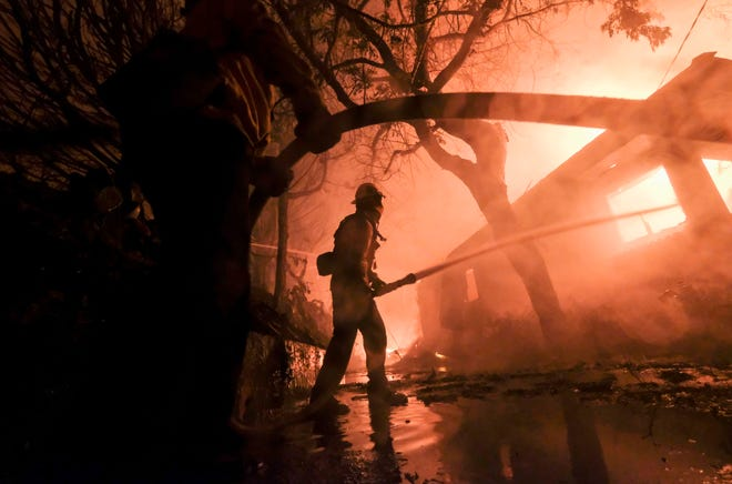 Firefighters battle the Woolsey Fire as it burns a home in Malibu in this file photo.