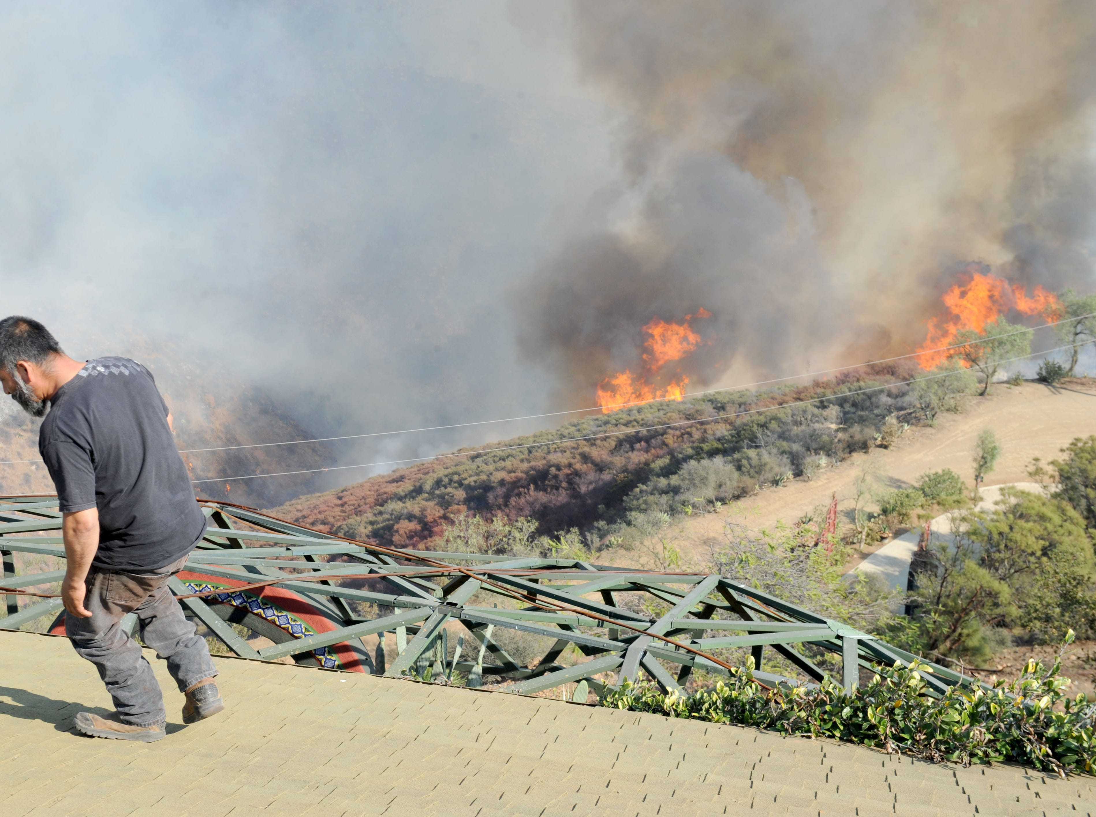 Juan Grenados watches the fire come up the canyon near the house of his friend Rick Mecagni at Mipolomol and Cotharin roads in the mountains of Ventura County. The Woolsey Fire continues to burn in the county.