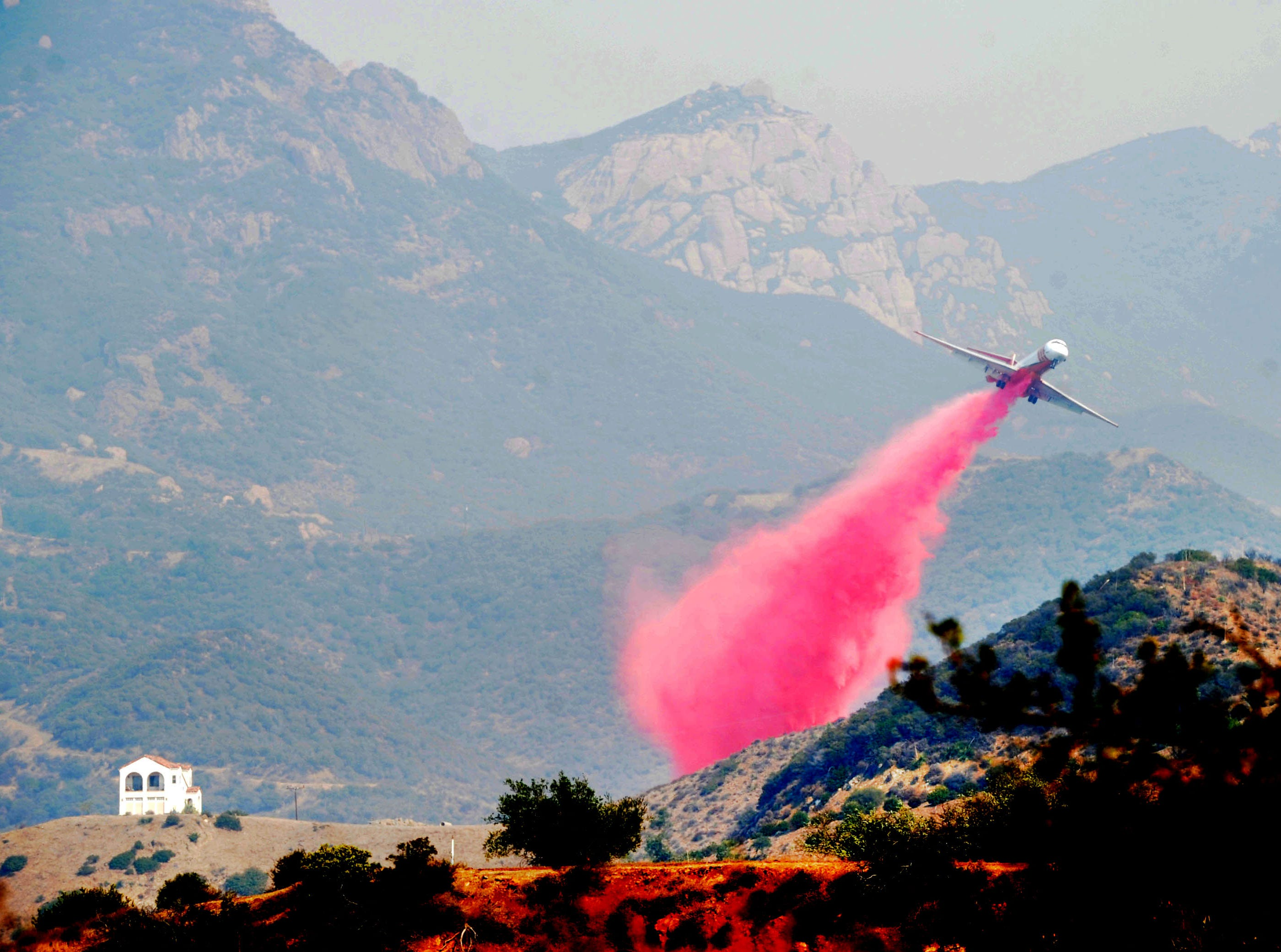 An airplane drops fire retardant Saturday on houses at Mipolomol and Cotharin roads in the mountains of Ventura County. The Woolsey Fire continues to burn in the county. Sandstone Peak is behind the plane.