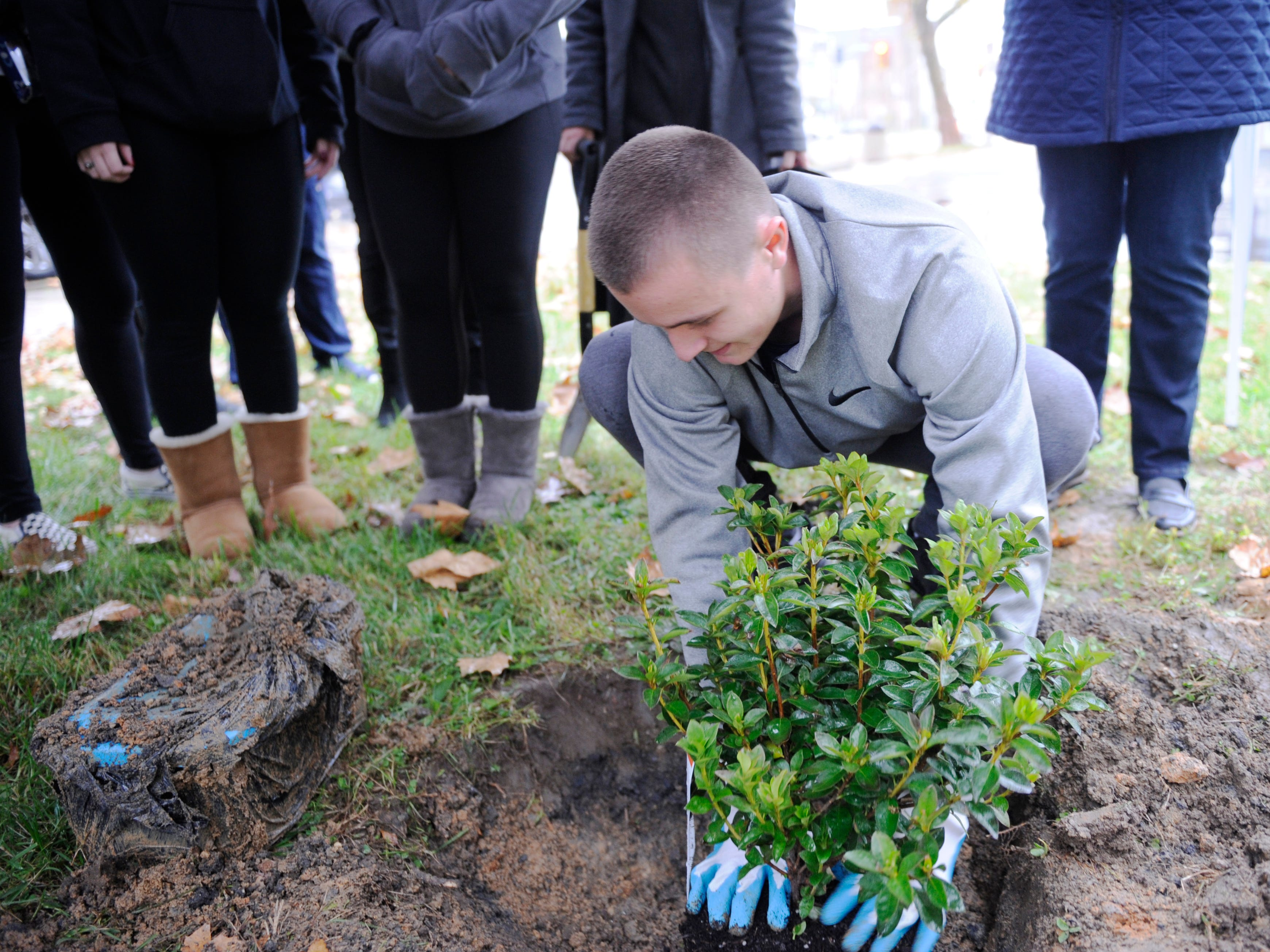 Nick Vicente, a St. Augustine senior, helps plant a flowering shrub in the space vacated by a time capsule that his second grade Bishop Schad class buried a decade ago.