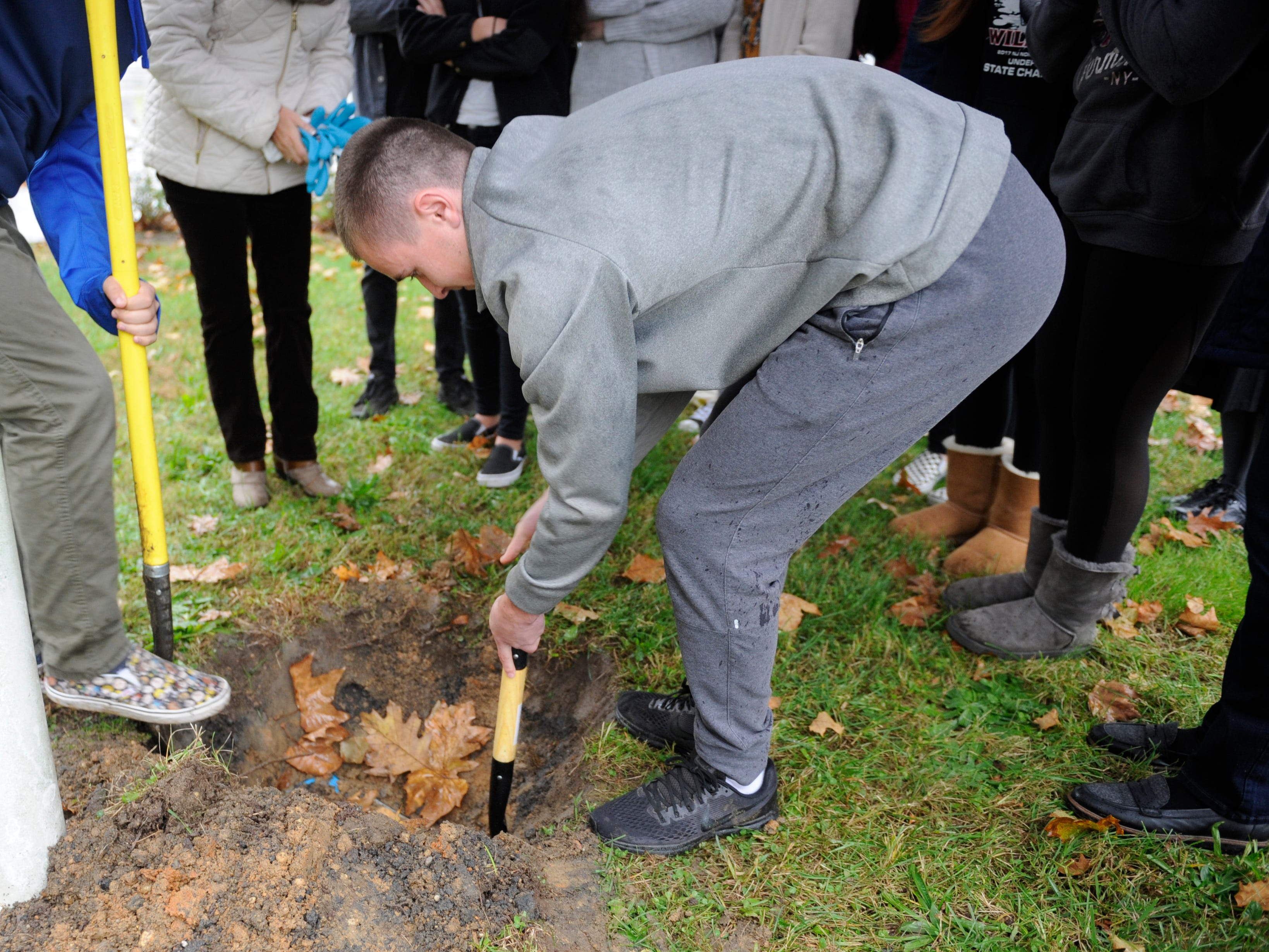 Nick Vicente, a St. Augustine senior, helps dig up a time capsule that his second grade Bishop Schad class buried a decade ago.