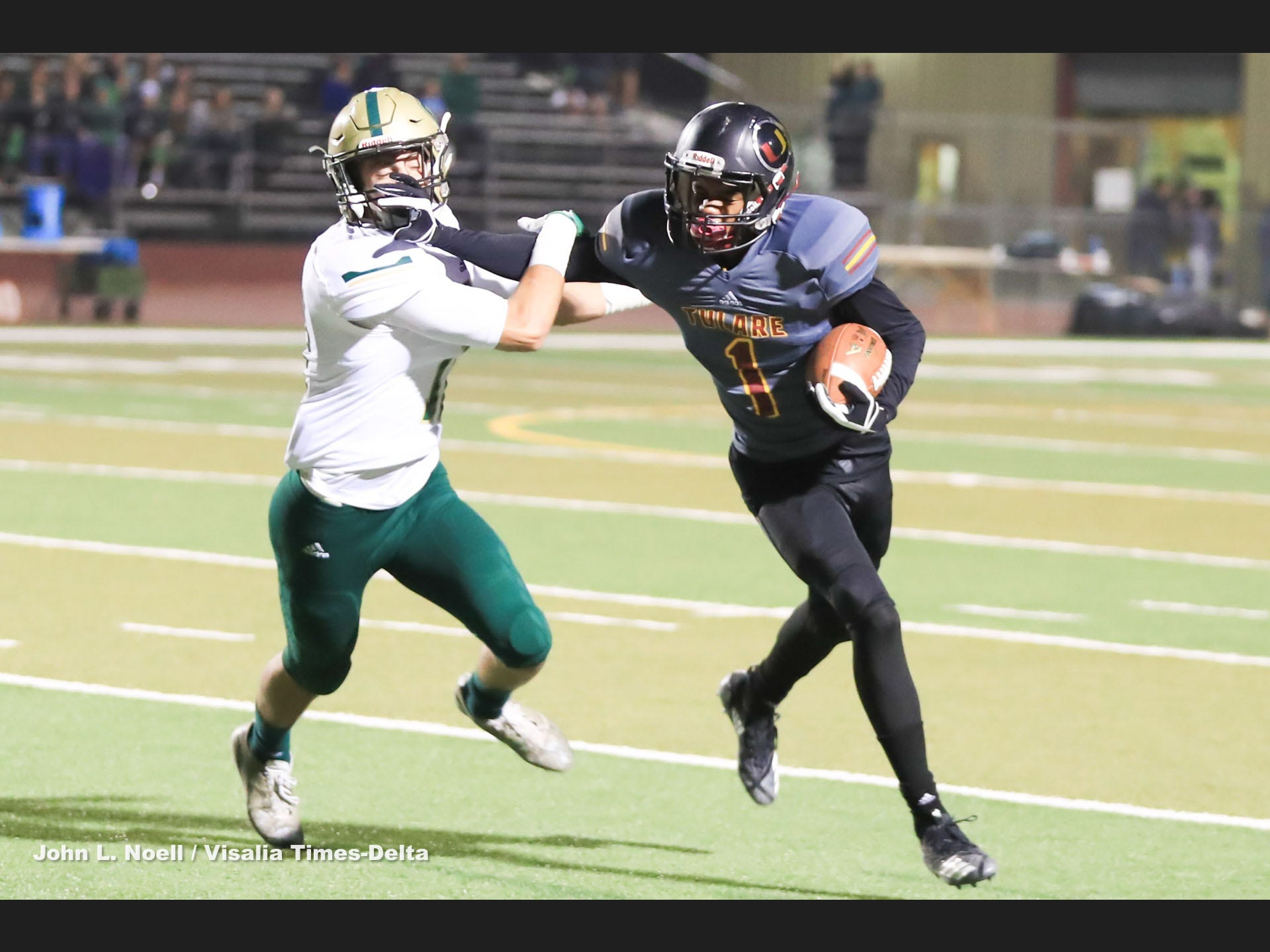 Tulare Union's  Willie James (1) straight arms Nick Sill (11) from Garces Memorial in a Central Section Division II quarterfinal high school football game at Bob Mathias Stadium on Nov 9th, 2018.
