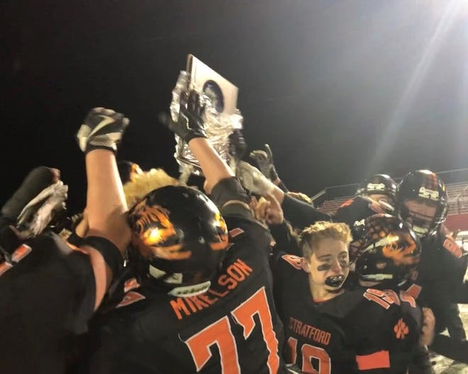 Stratford players celebrate with a plaque after beating Spencer/Columbus Catholic 22-6 in a WIAA Division 5 state semfinal matchup on Friday in Medford.