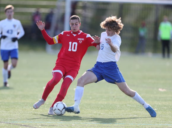 Somers' Lucas Fecci (10) battles for possession with Queensbury's Ray Jones (5) during their 2-1 win over Queensbury in the Class A Boys State Soccer Semifinalat Mount St. Mary College in Newburgh on Saturday, November 10, 2018.