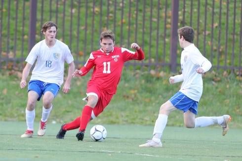 Somers' Jon Riina (11) splits the Queensbury defense during their 2-1 win over Queensbury in the Class A Boys State Soccer Semifinal at Mount St. Mary College in Newburgh on Saturday, November 10, 2018.
