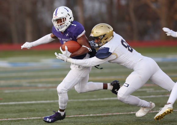 New Rochelle's Omari Walker (1) tries to break away from Newburgh's Justin Sennett  (8) during the Class AA regional championship game at Mahopac High School Nov. 9, 2018.
