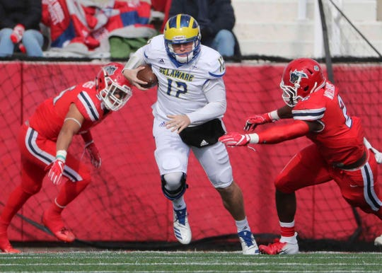 Delaware quarterback Pat Kehoe scrambles for a gain in the first quarter between Seawolves Shane Lawless (left) and Casey Williams at Stony Brook Saturday.