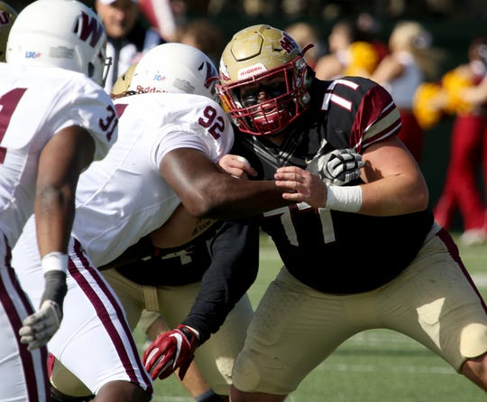 Midwestern State's A.J. Roland (77) blocks West Texas A&M's Henry Paul Saturday, Nov. 10, 2018, at Memorial Stadium. The Mustangs defeated Buffs 24-23 in overtime.