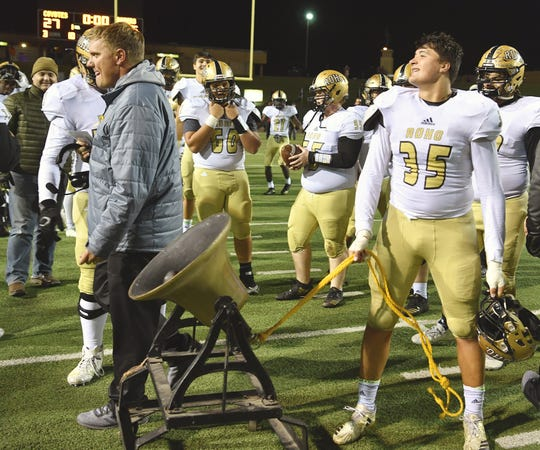 Rider senior Joshua Rodriguez (35) rings the victory bell following the Raider's win over the Coyotes Friday night at Memorial Stadium. Rider defeated Wichita Falls High, 45-27.