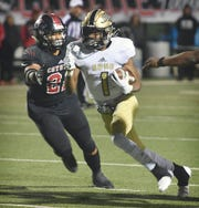 Rider runningback Samuel Manuel (1) cuts inside as Wichita Falls High defender Makkedah Brown (21) moves in for the tackle Friday night at Memorial Stadium. Rider defeated Wichita Falls High, 45-27.