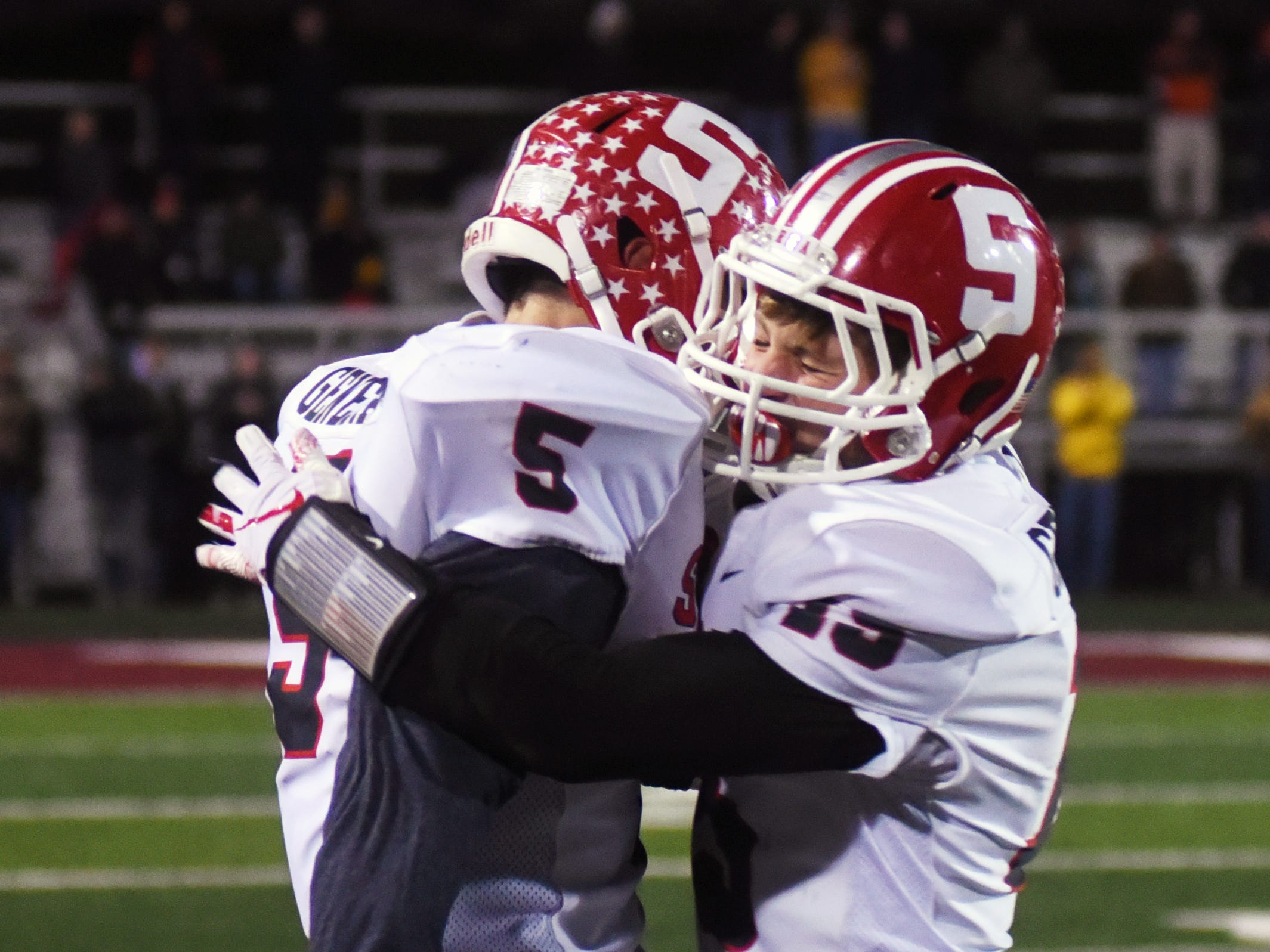Shay Taylor, left, is congratulated by teammate Alec Ogle after intercepting a pass in the second quarter against Granville.