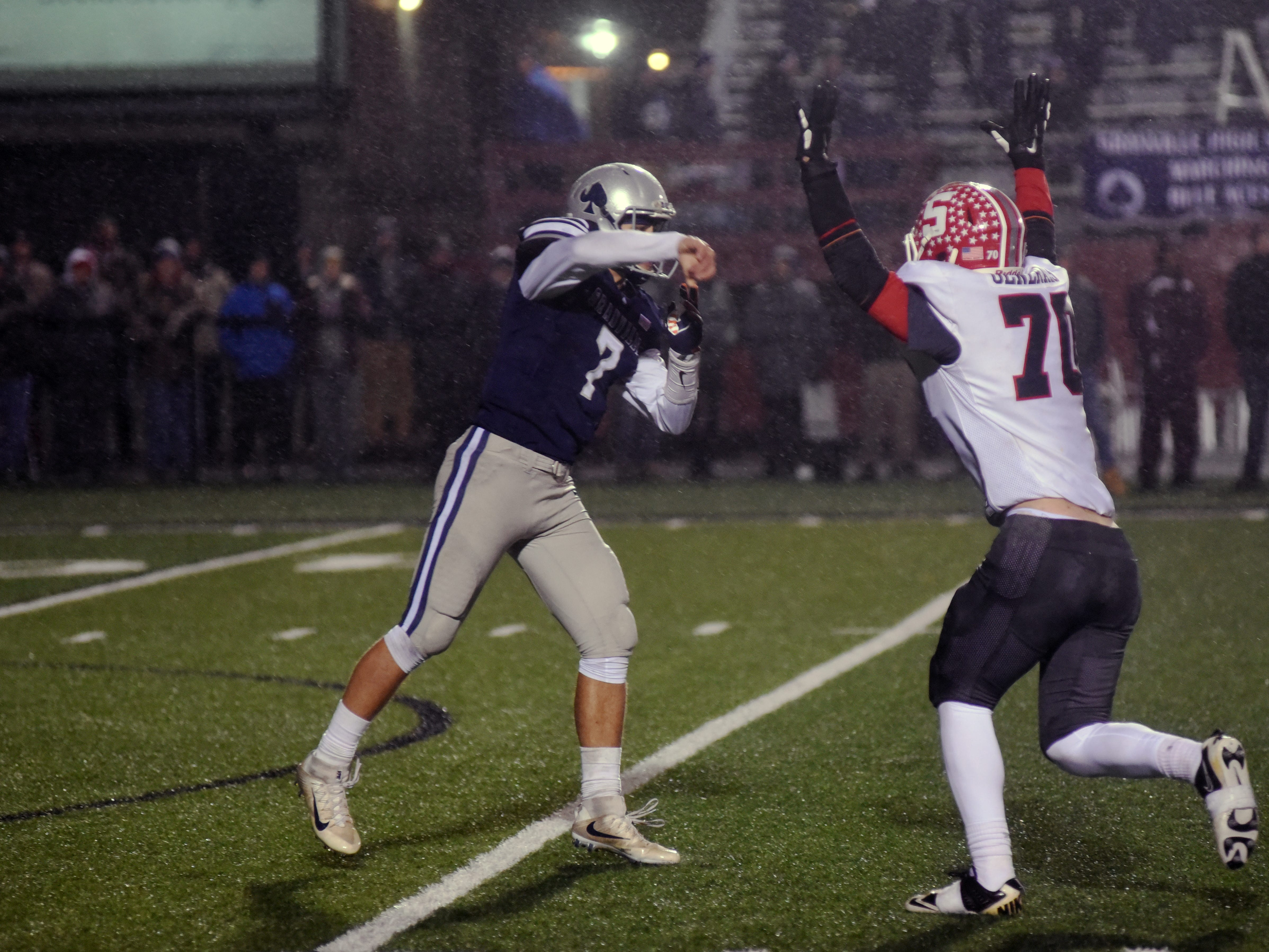 Granville's Cameron Crouch throws over a rushing Owen Loughman, of Sheridan, in a Division III, Region 11 semifinal at White Field.
