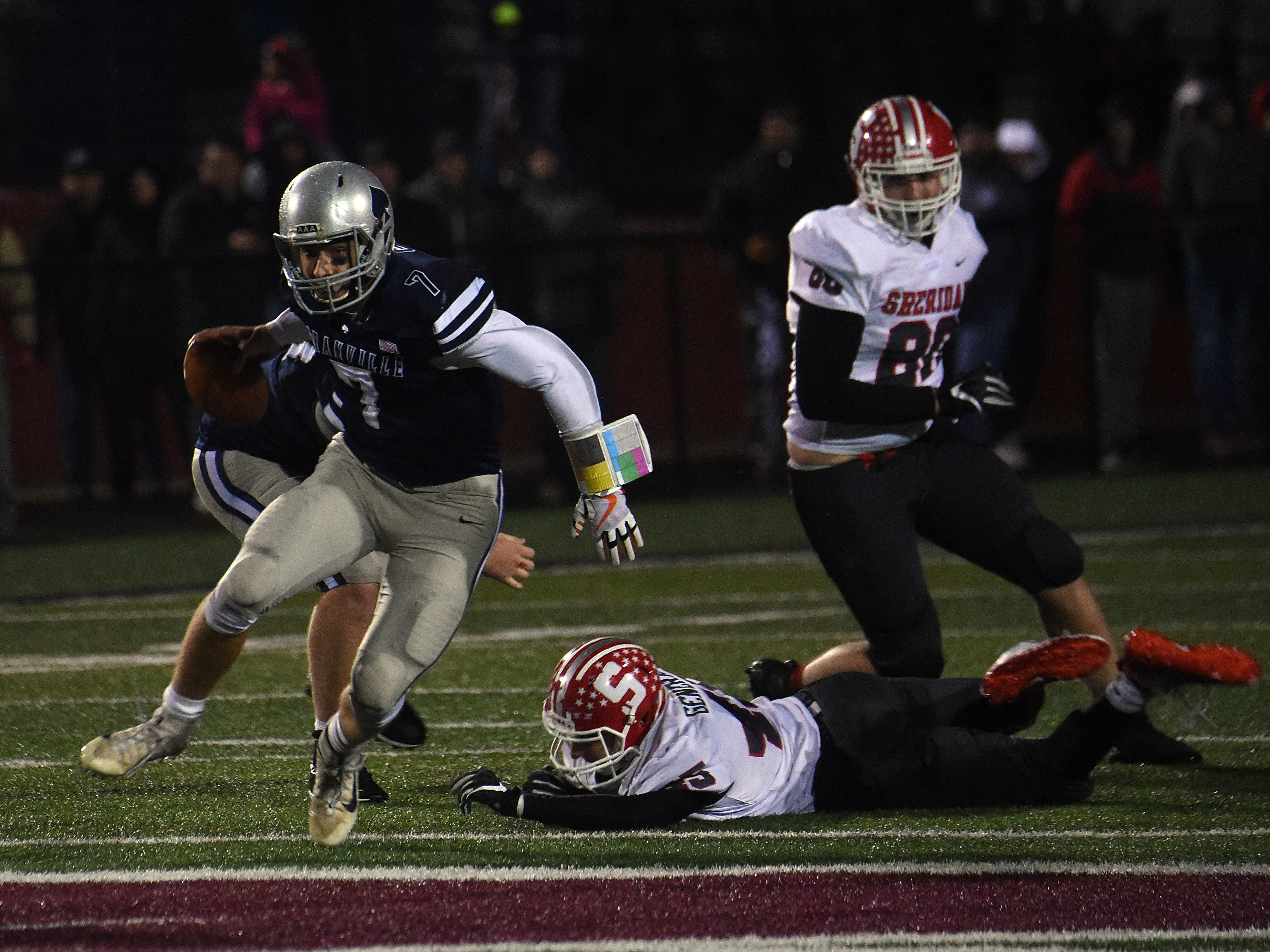 Granville senior quarterback Cameron Crouch scrambles past Sheridan junior defender Alec Ogle. The Generals defeated the Blue Aces 20-7 in a Division III, Region 11 semifinal on Friday, Nov. 9, 2018 at White Field in Newark.