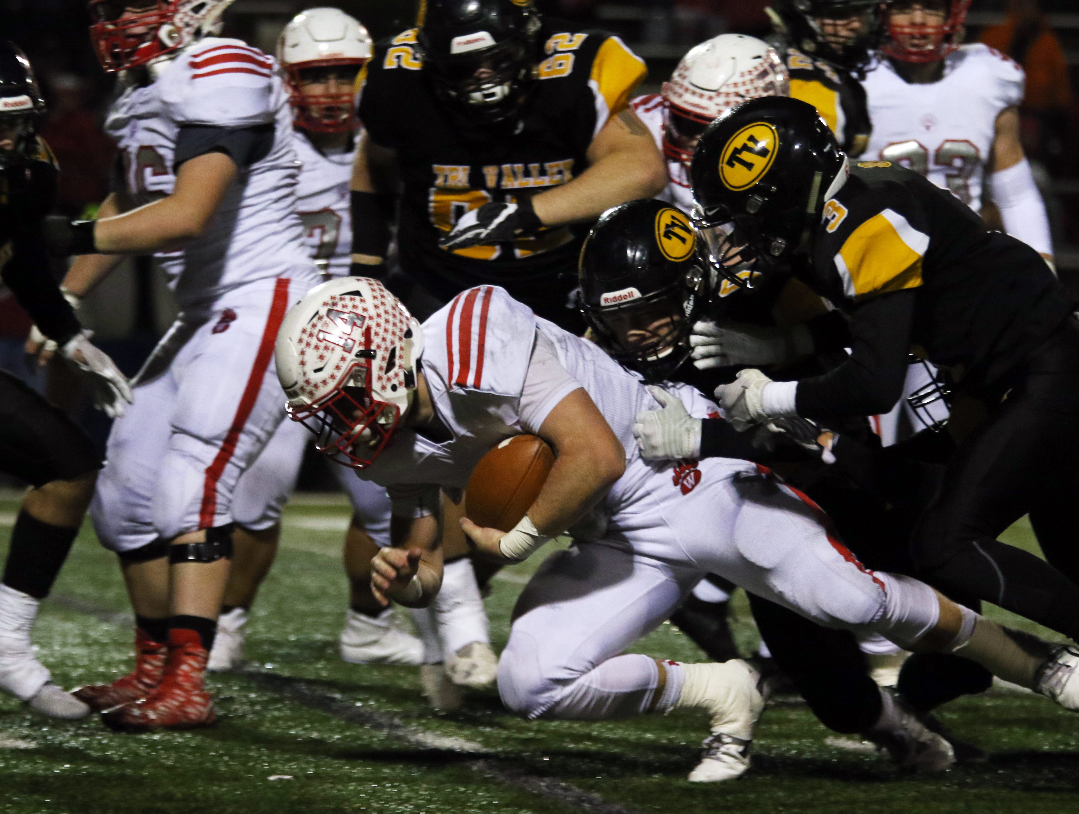 A pair of Tri-Valley defenders tackle a Wadsworth ball carrier.