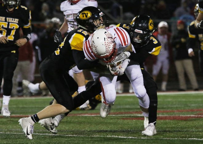 Tri-Valley's Cade Sterling (3) and Graham Cameron (12) tackle a Wadsworth ball carrier Friday night at Dover's Crater Stadium.