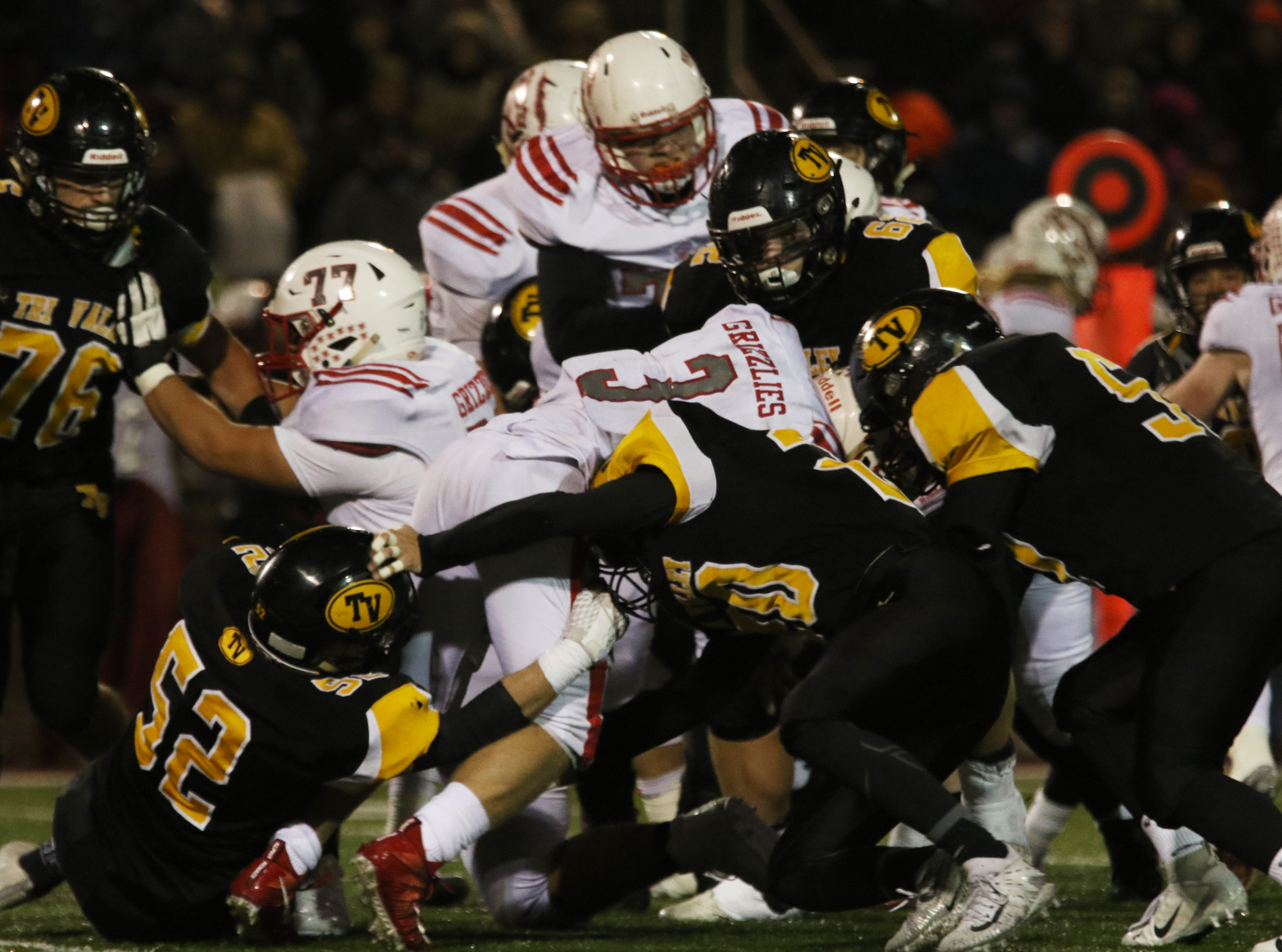 Tri-Valley defenders, including Tom Reiss (52) tackle Wadsworth's Dom Loparo.