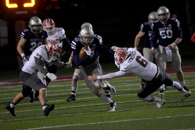 Granville junior wide receiver Zach Walsh (center) runs through Sheridan senior defenders Nick Ranalli (left) and Ethan Heller (right). The Generals defeated the Blue Aces 20-7 in a Division III, Region 11 semifinal on Friday, Nov. 9, 2018 at White Field in Newark.