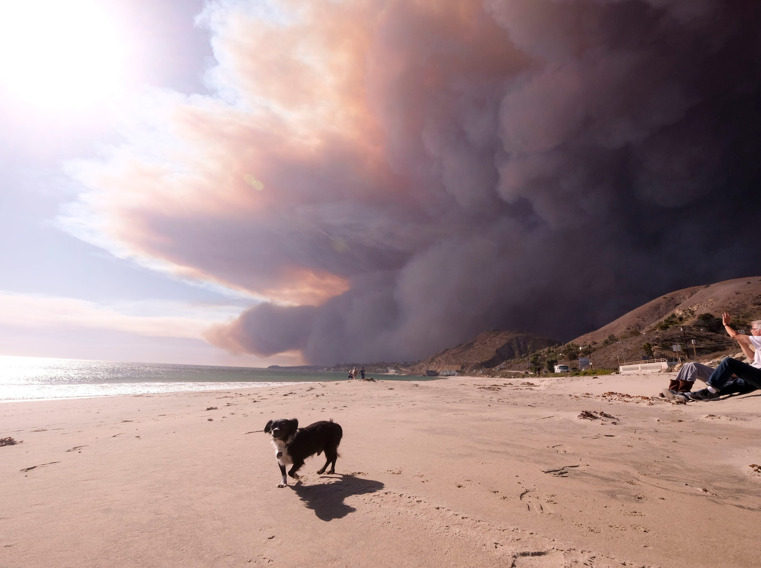 People enjoy the day in the beach as the heavy smoke rises over the the Santa Monica Mountains during the Woolsey fire in Malibu, Calif., on  Friday.