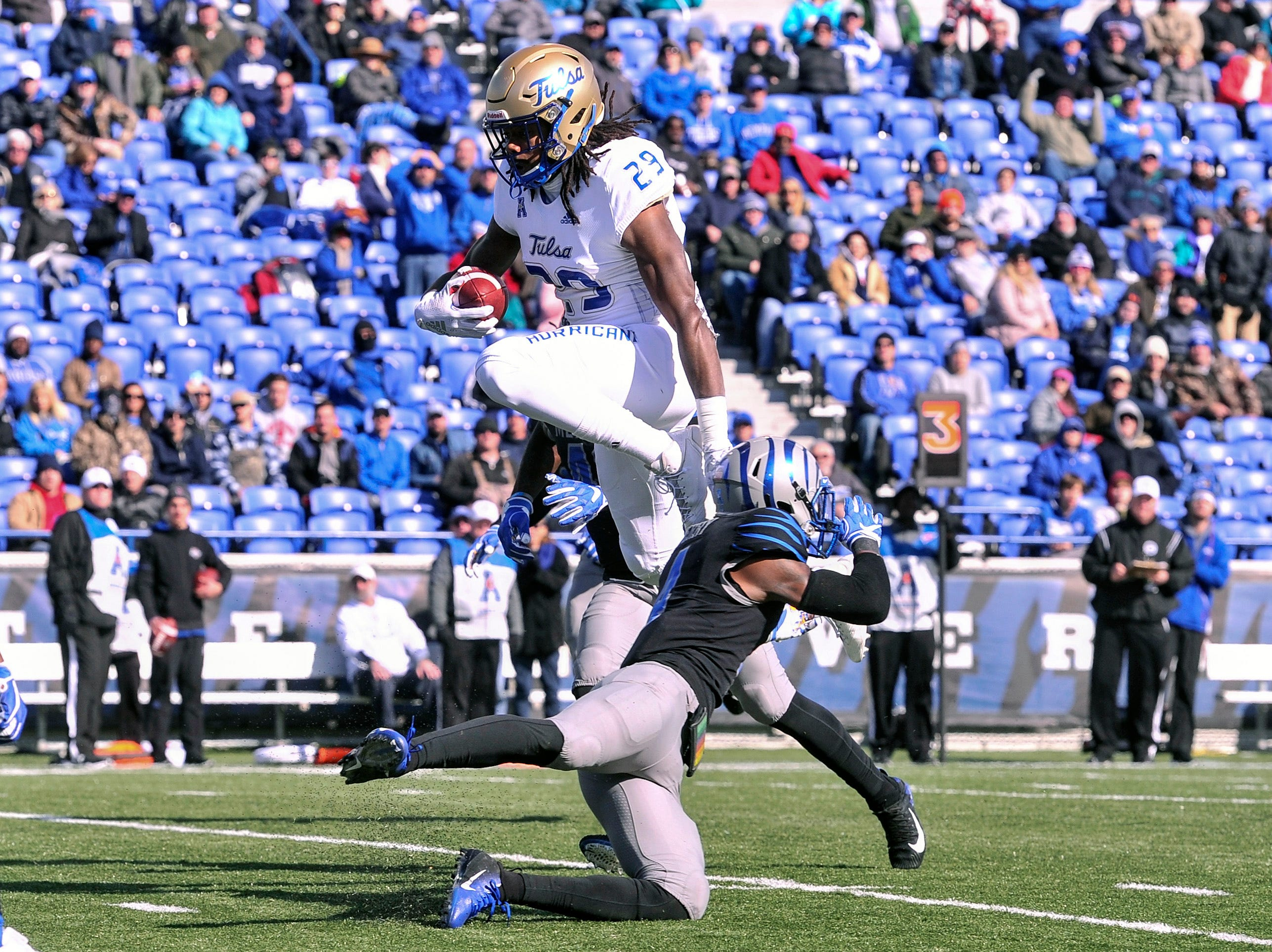 Tulsa Golden Hurricane wide receiver Justin Hobbs (29) leaps over Memphis Tigers defensive back Josh Perry (4) during the second half at Liberty Bowl Memorial Stadium.