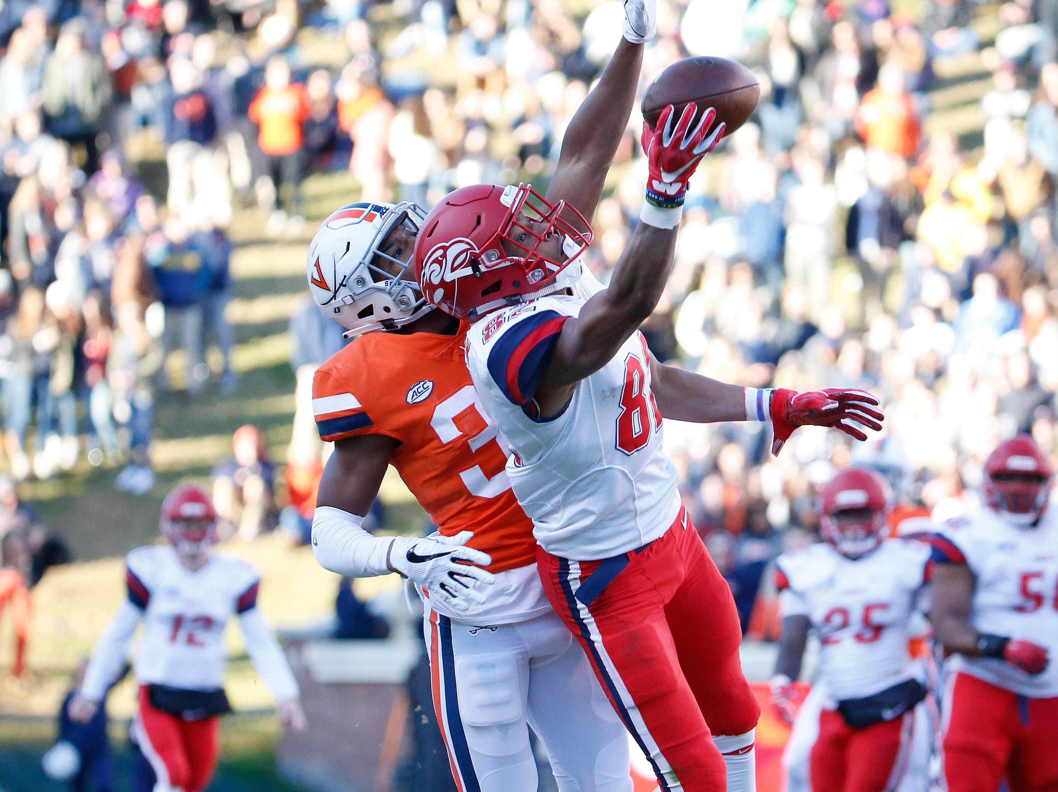 Liberty Flames wide receiver B.J. Farrow (82) catches a pass in front of Virginia Cavaliers cornerback Bryce Hall (34) during the first half at Scott Stadium.