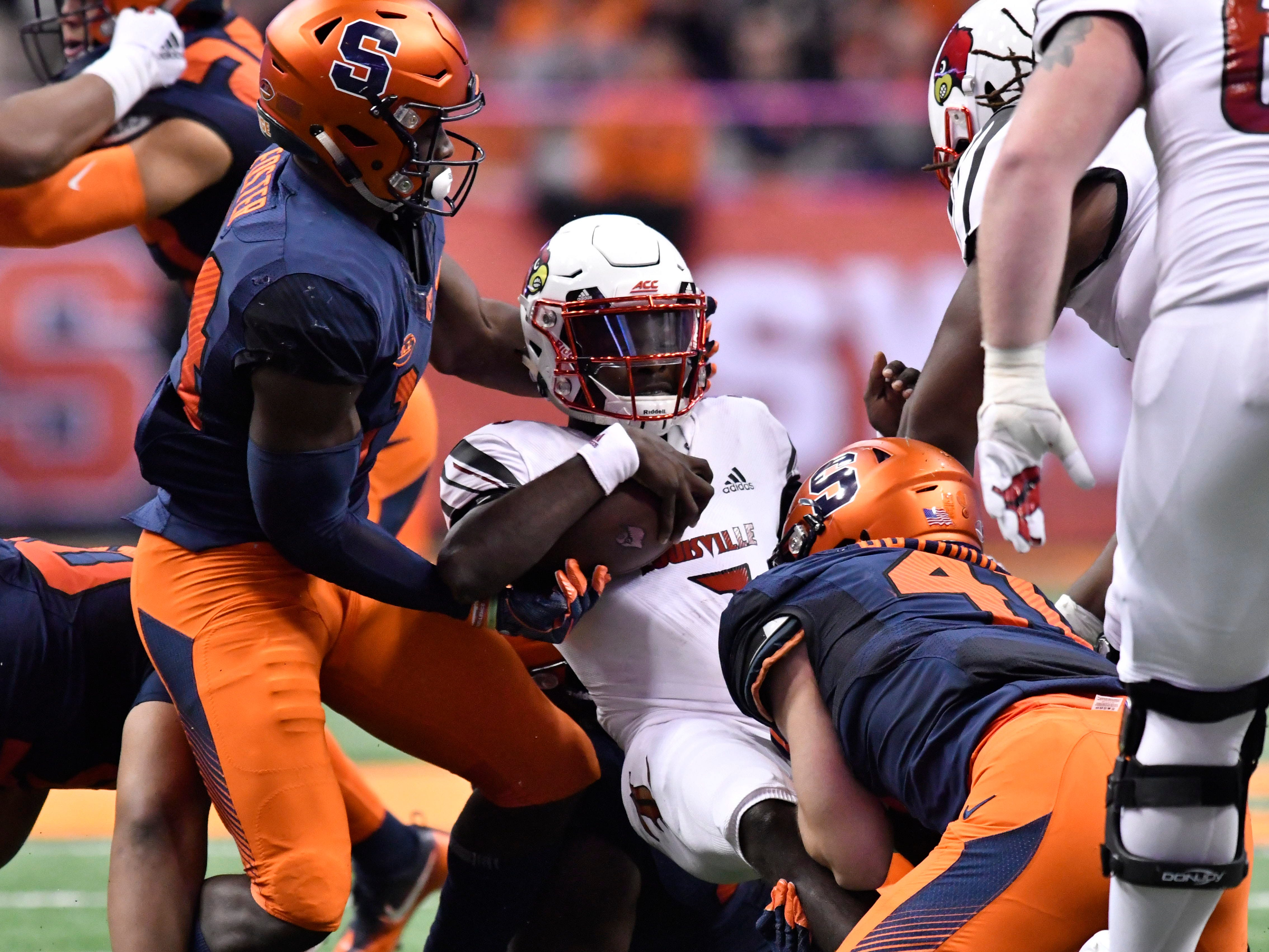 Louisville Cardinals quarterback Malik Cunningham (3) is tackled by Syracuse Orange linebacker Ryan Guthrie (41) and defensive back Evan Foster (14) during the second quarter at the Carrier Dome.