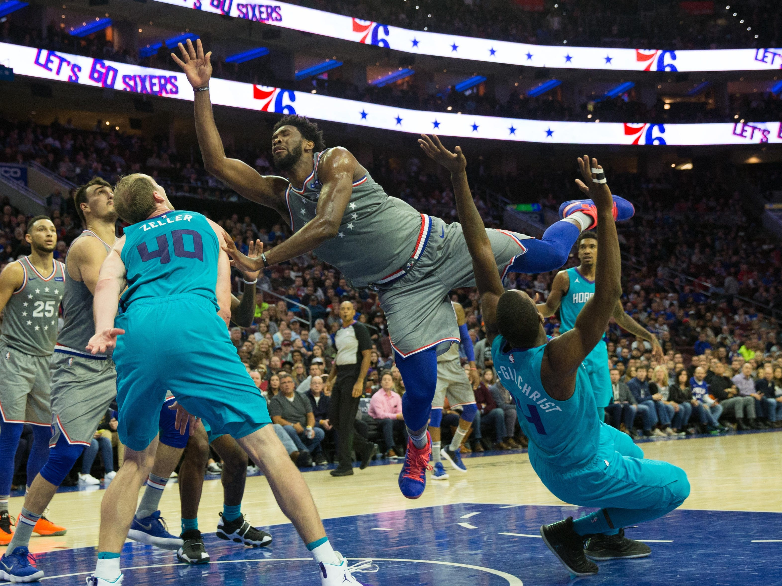 Nov. 9: Sixers center Joel Embiid (21) goes careening down the lane between Hornets defenders Cody Zeller (40) and Michael Kidd-Gilchrist (14) during the fourth quarter in Philadelphia.