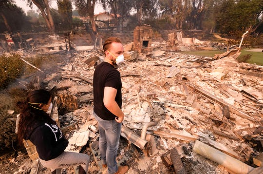 Alexander Tobolsky, right, and his girl friend Dina Arias, return to his home where burned out by the fire in Malibu, Calif., Saturday, Nov. 10, 2018.  Officials took advantage of temporarily calm conditions Saturday to assess damage from the blaze that's burned 109 square miles outside downtown Los Angeles.