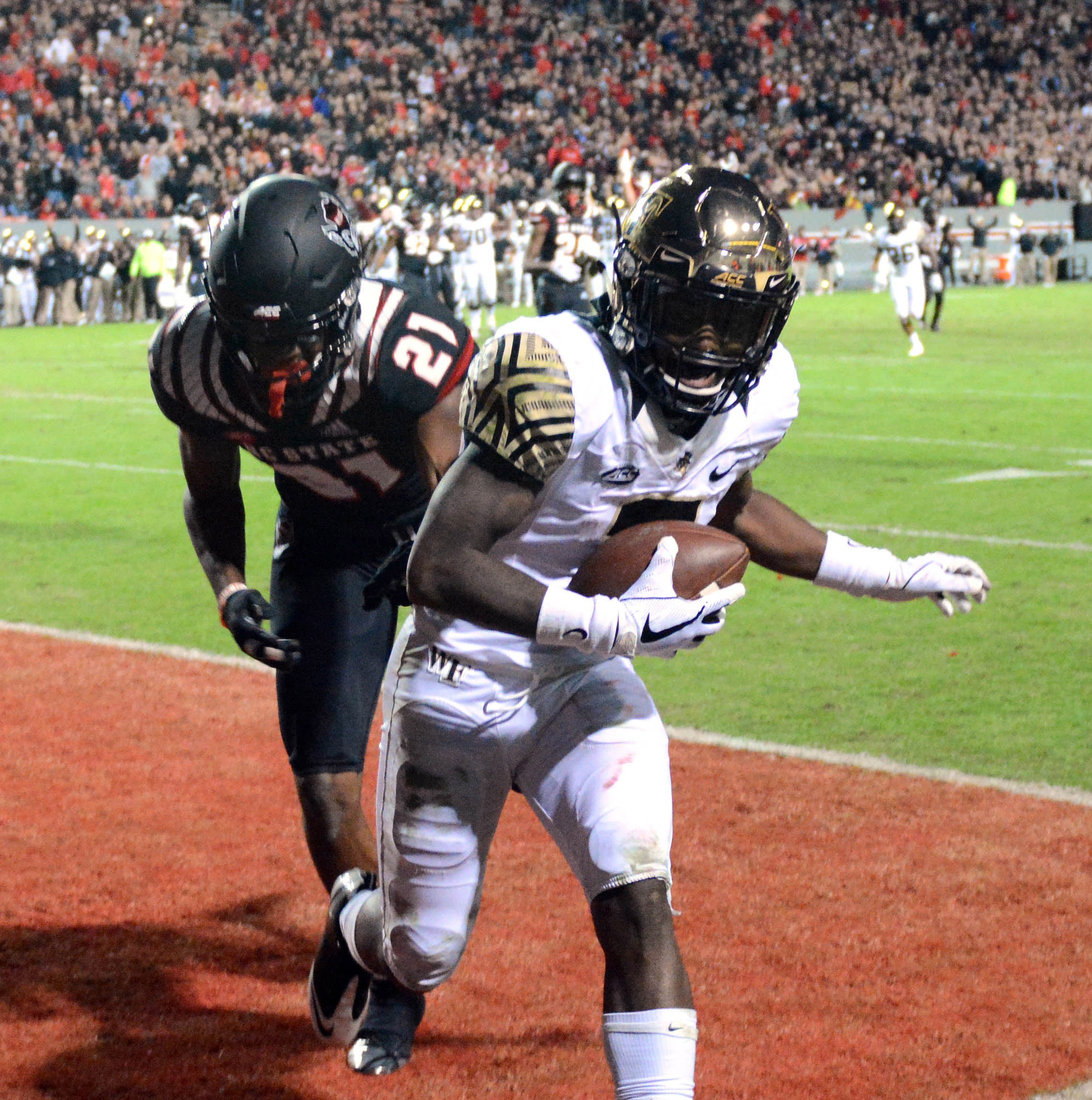 Wake Forest Demon Deacons receiver Greg Dortch (3) scores a touchdown in front of North Carolina State Wolfpack defensive back Stephen Griffin (21) during the second half at Carter-Finley Stadium.