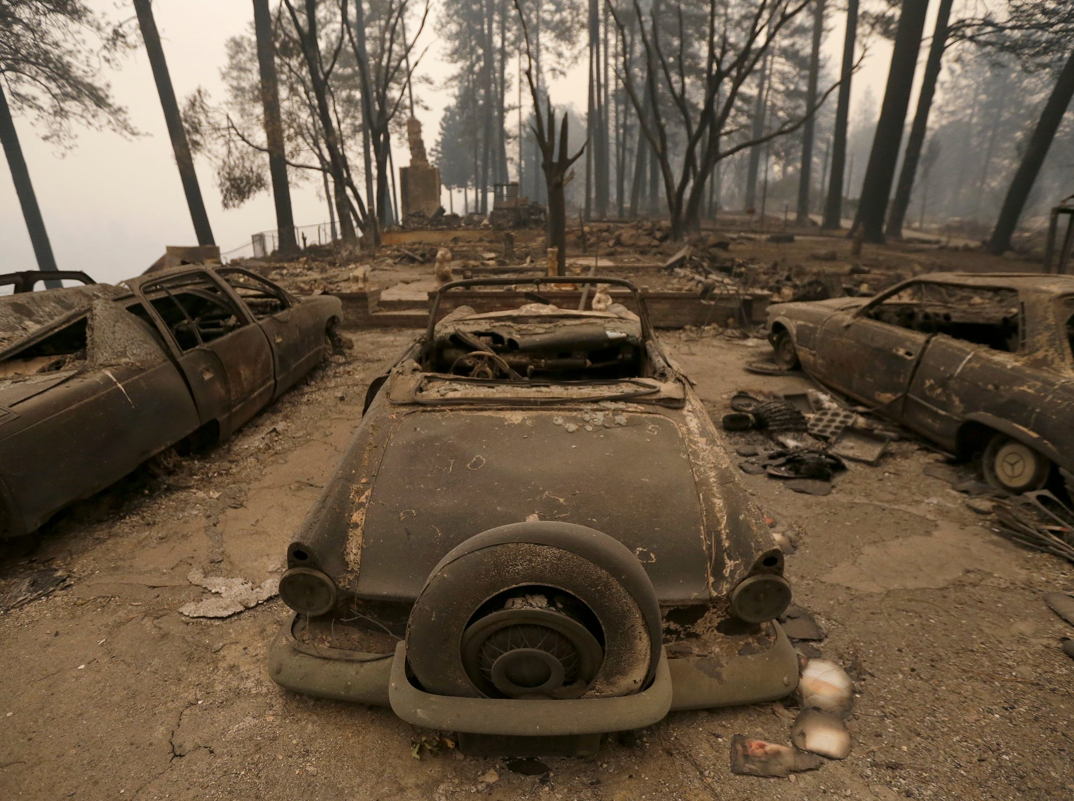 Three cars destroyed by a wildfire sit at a burned out home Friday, in Paradise, Calif. Authorities have confirmed that at least six people have died in the fire that has consumed more than 70,000 acres and destroyed at least 2,000 structures.
