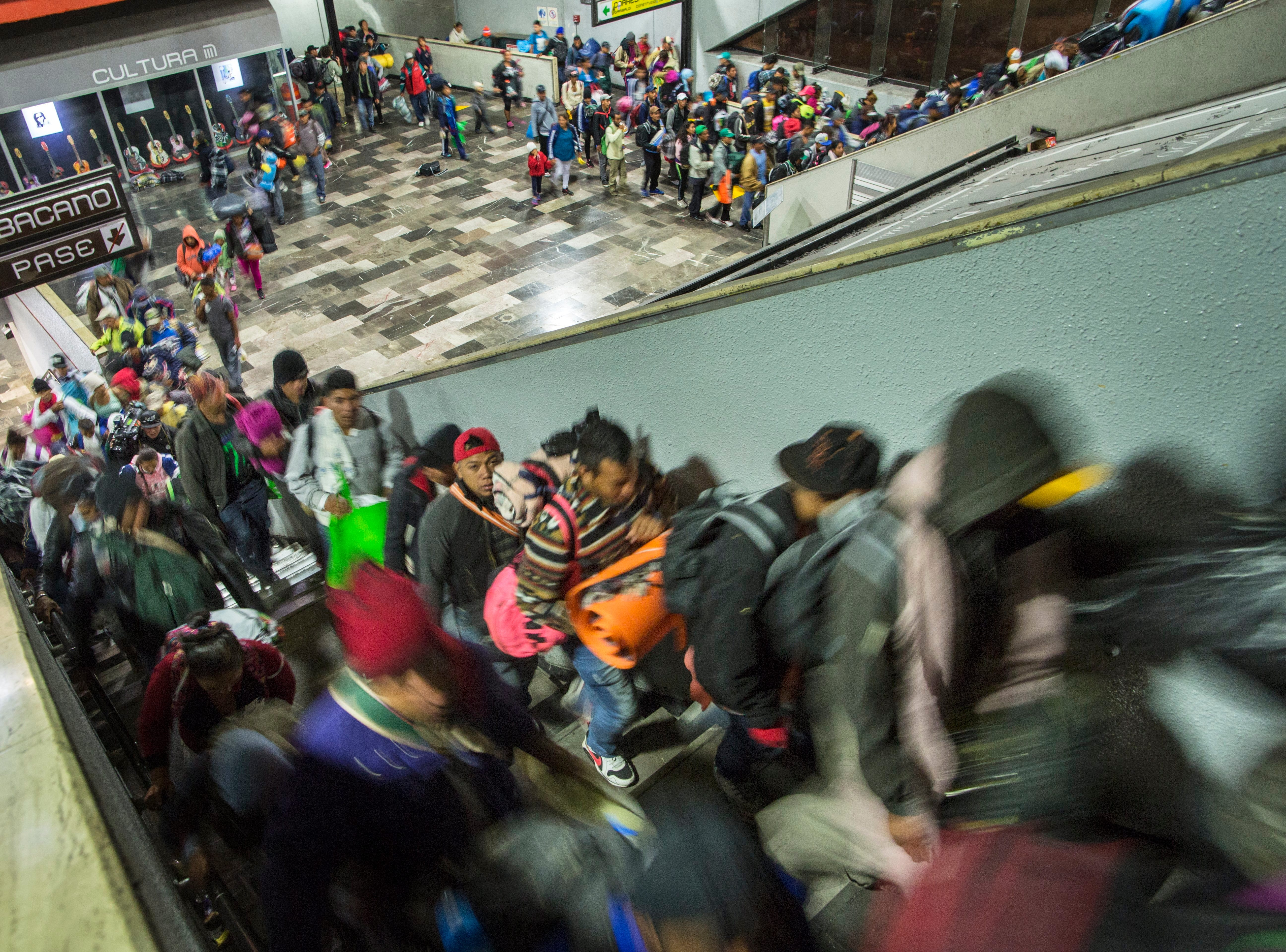 Central American migrants ride an escalator at a subway station as they resume their journey north after leaving the temporary shelter at the Jesus Martinez stadium, in Mexico City, Saturday, Nov. 10, 2018.