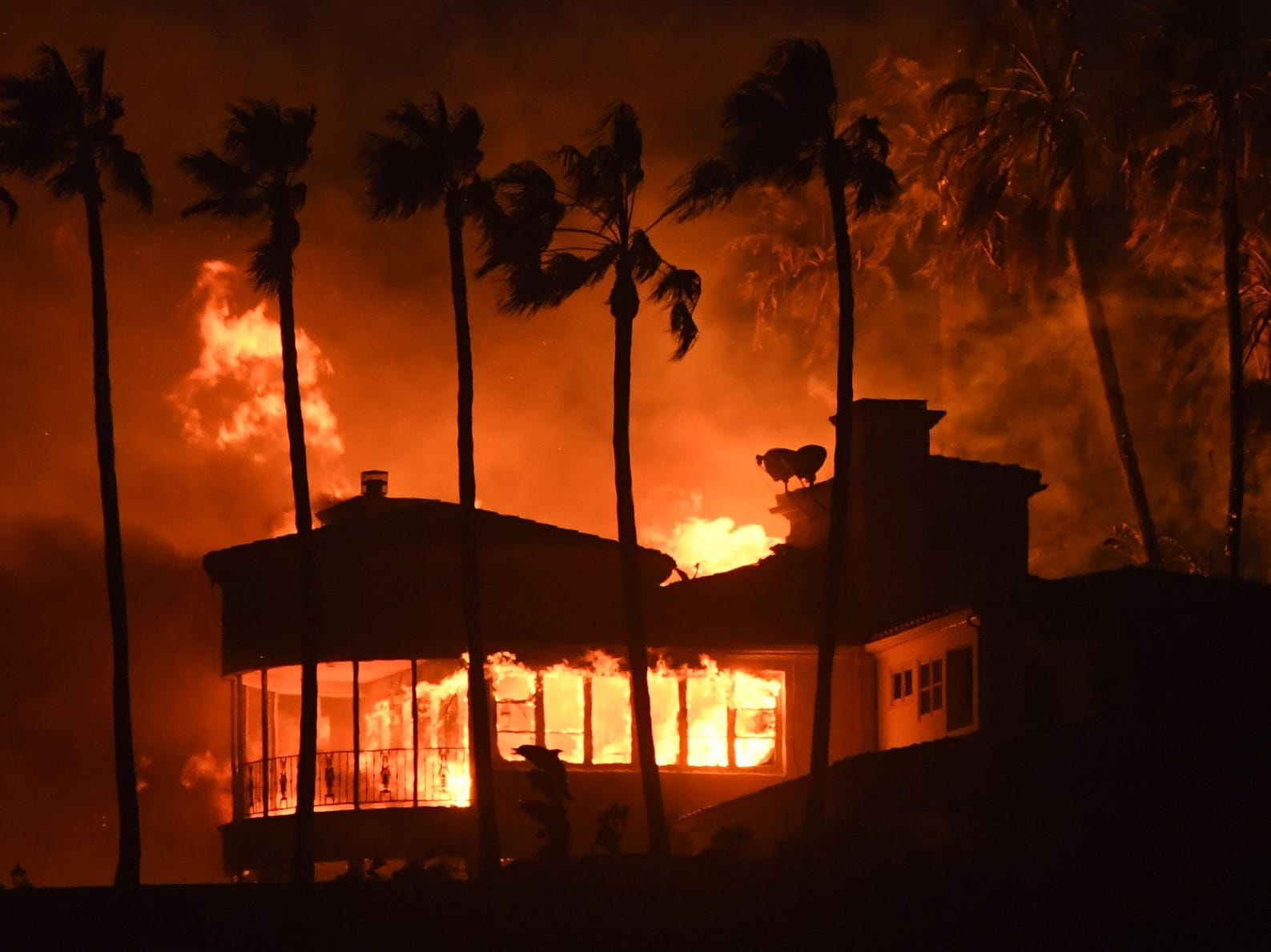 A house burns during the Woolsey Fire, Friday, in Malibu, Calif.