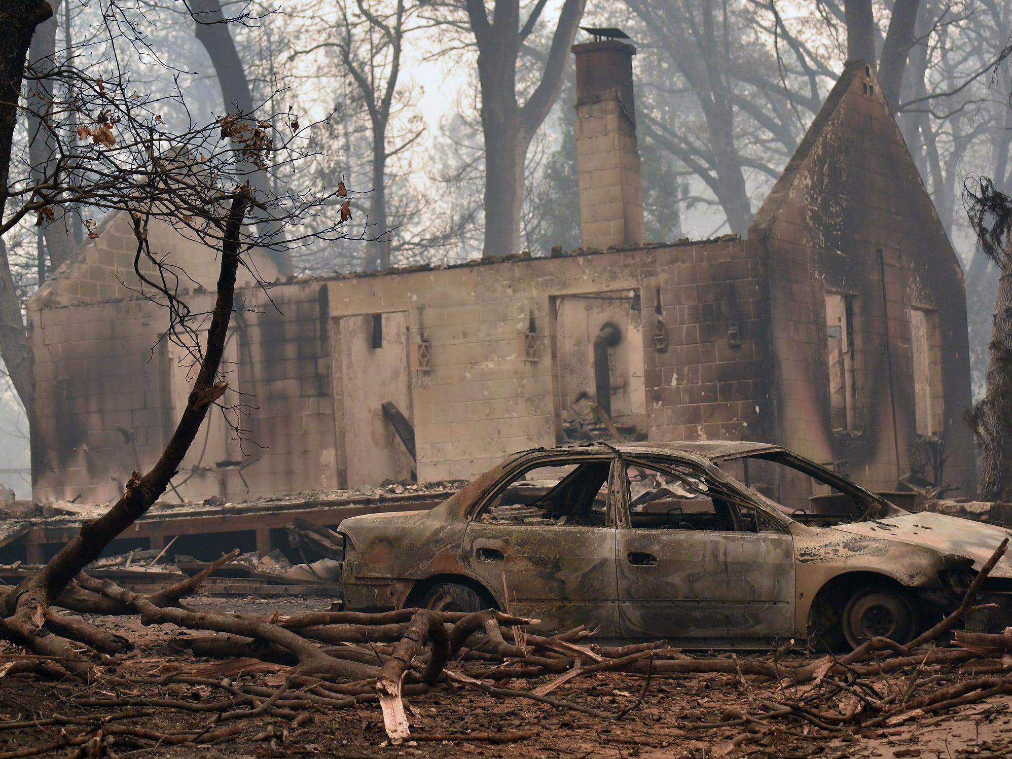 Smoke clouds the air above the remains of a burned-out house and car in Paradise, Calif., following the Camp Fire devastation on Friday.