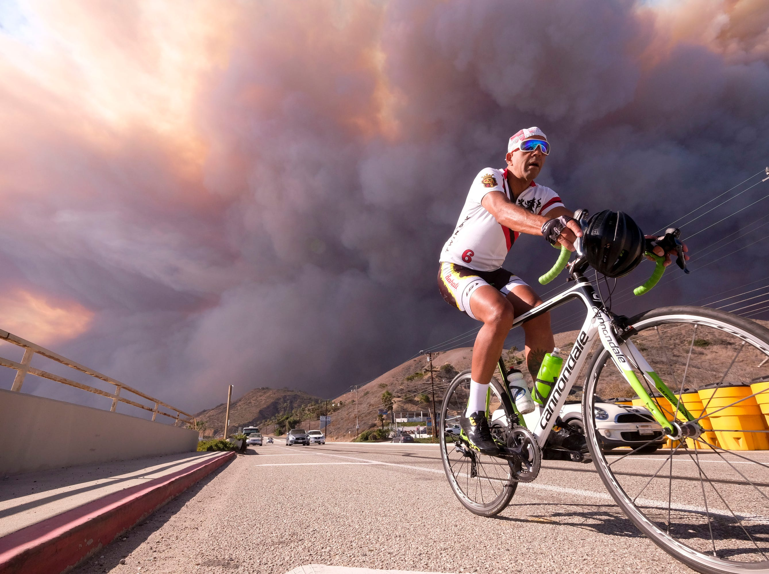 A man rides on along the Pacific Coast Highway as the heavy smoke rises over the the Santa Monica Mountains during the Woolsey fire in Malibu, Calif.