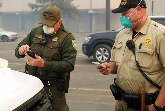 Butte County Sheriff's Deputy Brian Evans, left, checks his phone while assigning El Dorado County Sheriff's Deputy Craig Reimche to a new house to check for survivors during the grim search in Paradise, Calif. on Nov 10, 2018