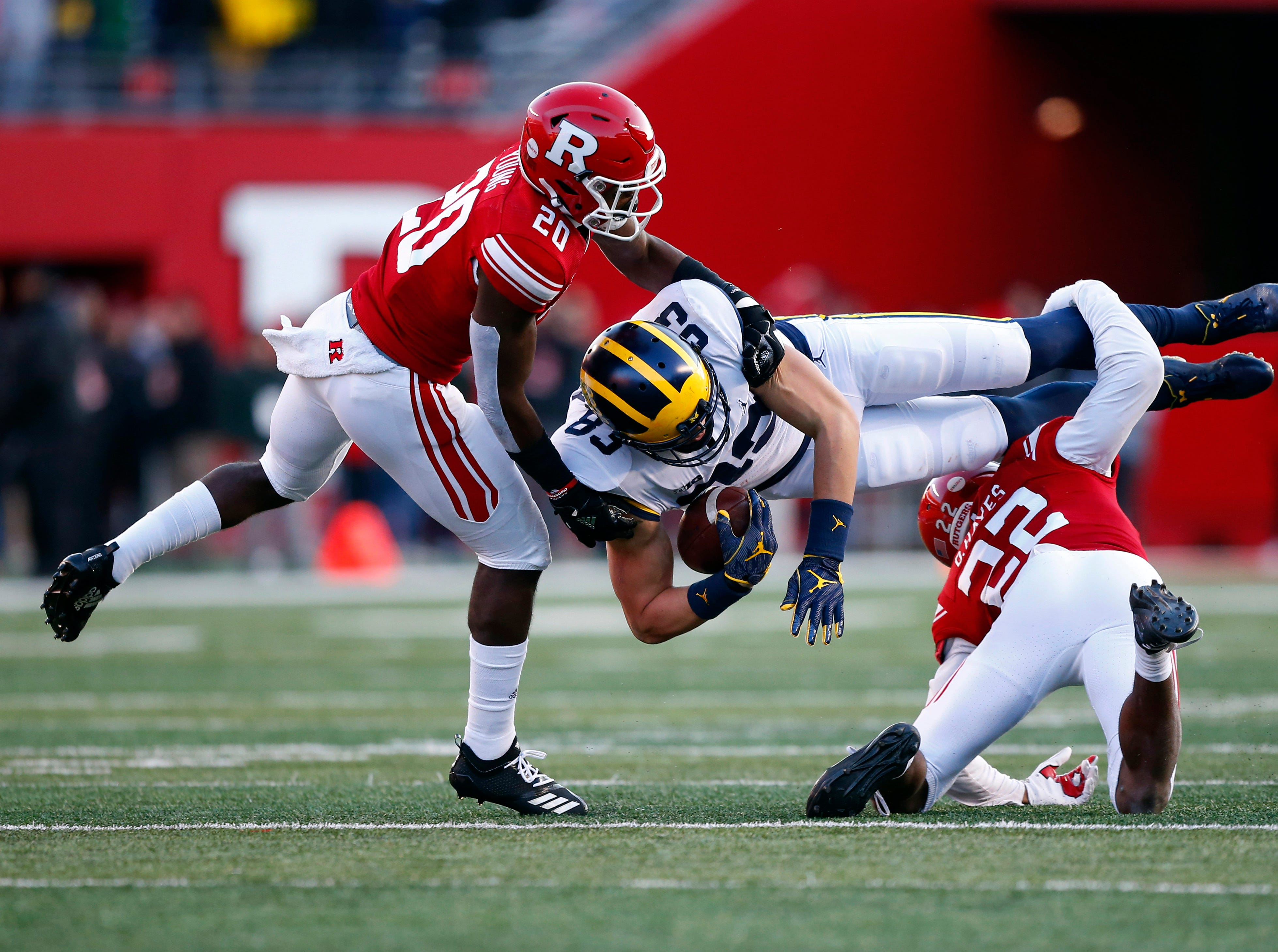 Michigan Wolverines tight end Zach Gentry (83)  is tackled by Rutgers Scarlet Knights defensive backs Avery Young (20) and Damon Hayes (22) during the first half at High Point Solutions Stadium.