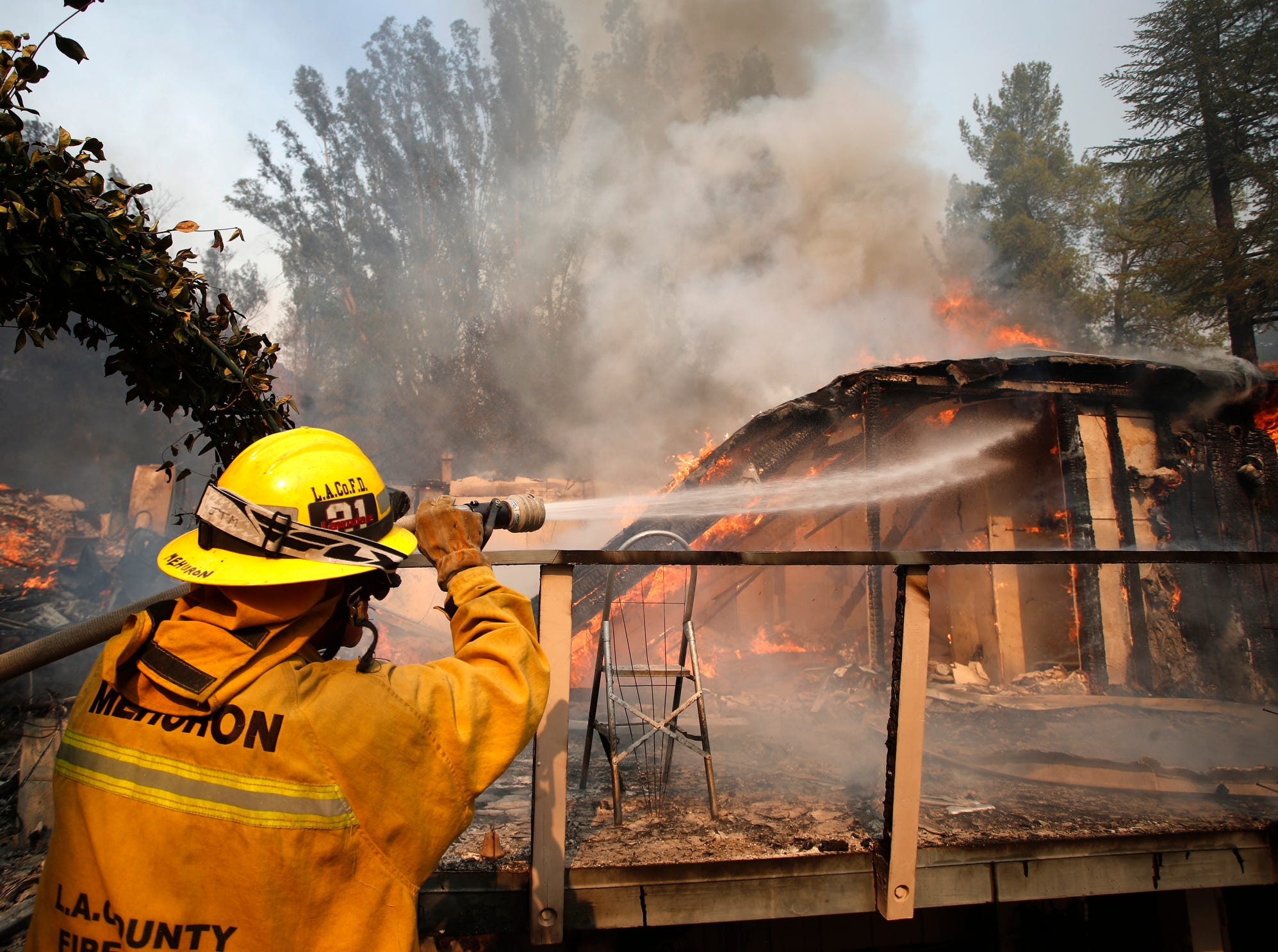 Firefighters battle a home on fire at the Malibu Lake community in Malibu, Calif., Friday.