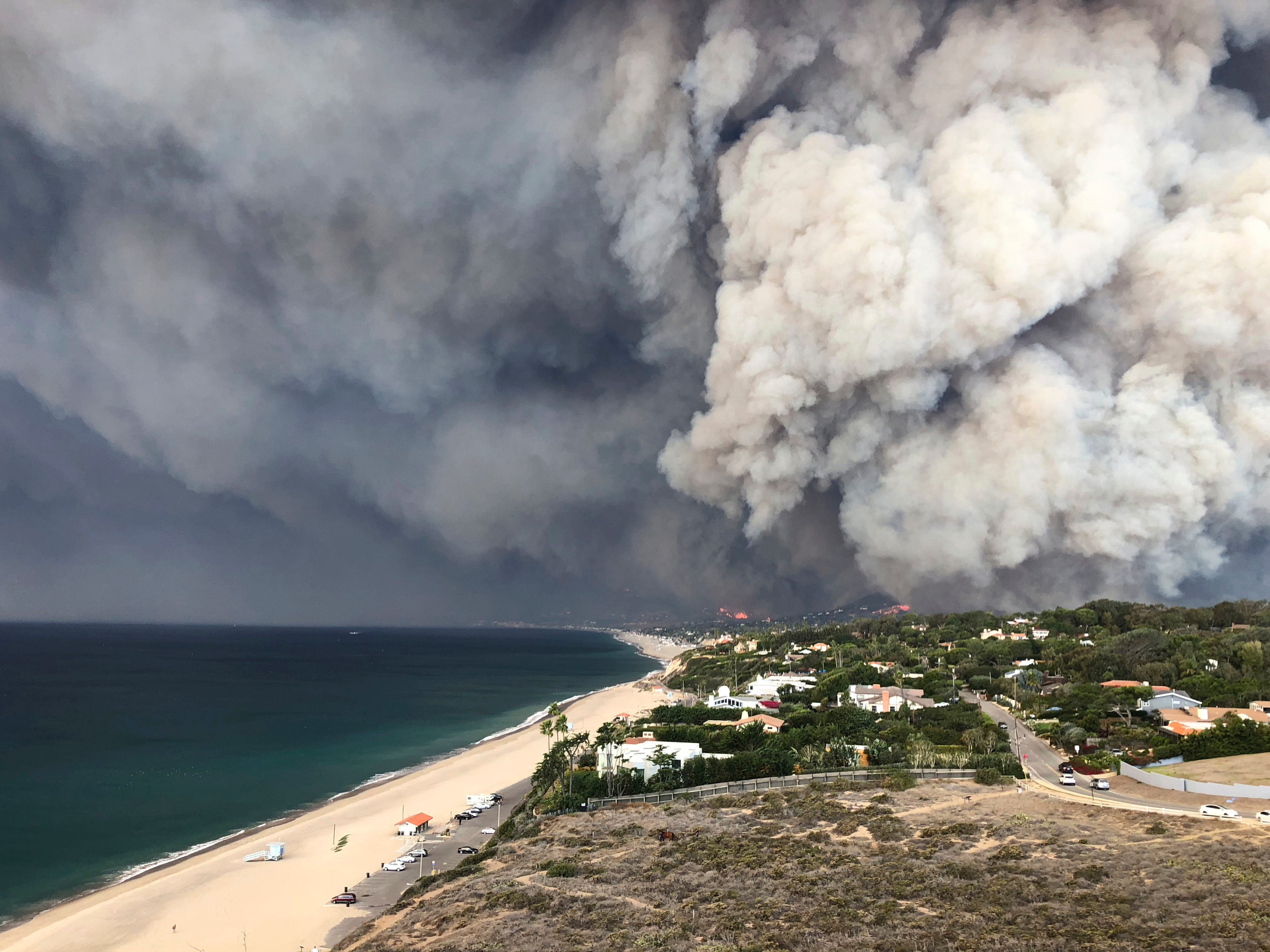 In this Friday, Nov. 9, 2018 photo, smoke from the wildires fills the air in Malibu, Calif.  Los Angeles County fire Chief Daryl Osby said Saturday that firefighters told him they were working in the toughest, most extreme conditions they had seen in their lives on Friday night. He says conditions are far better Saturday, with a lull in winds that are expected to return Sunday.