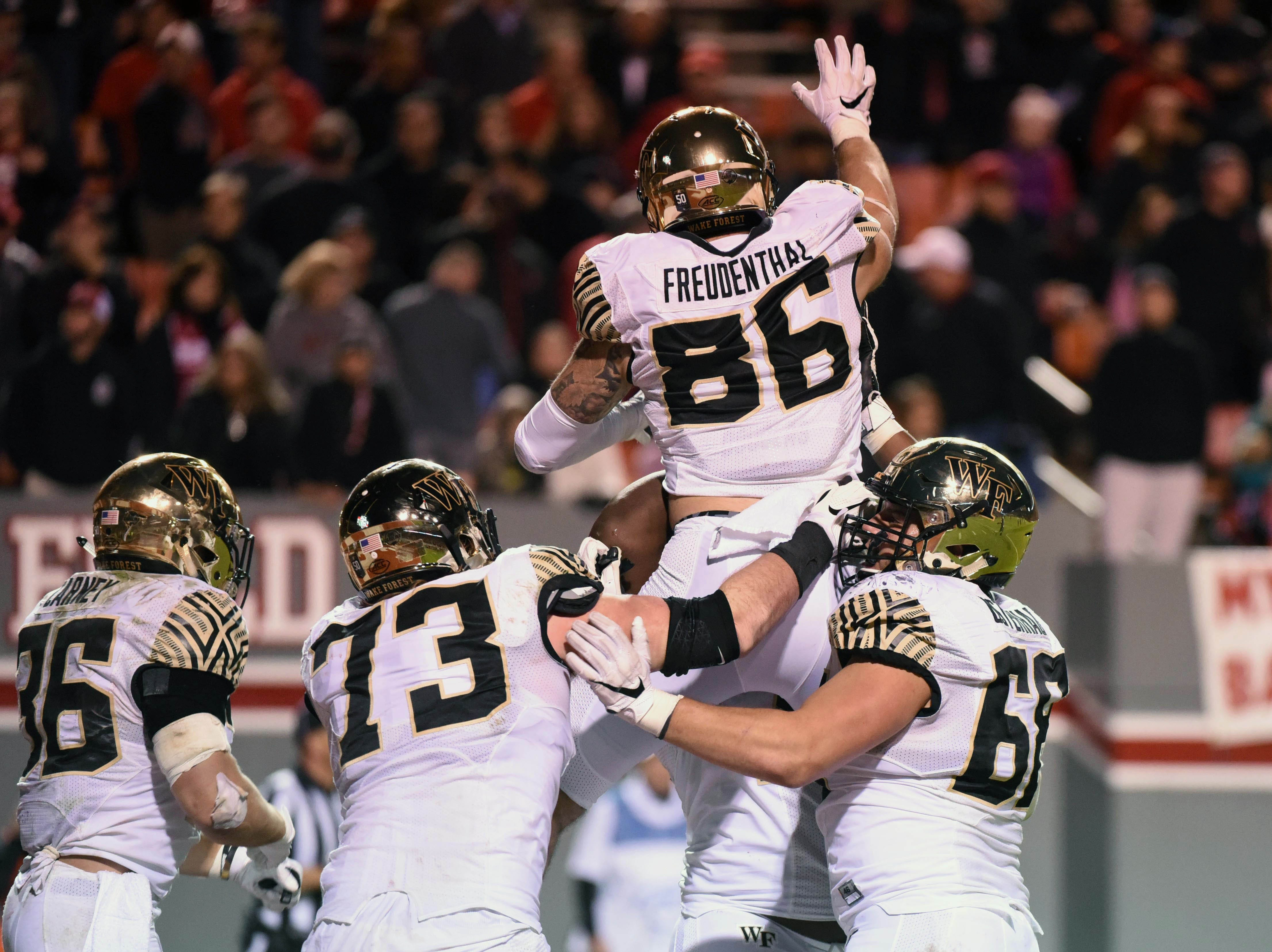 Wake Forest Demon Deacons tight end Jack Freudenthal (86) is greeted by teammates after scoring the game-winning touchdown during the second half against the North Carolina State Wolfpack at Carter-Finley Stadium.