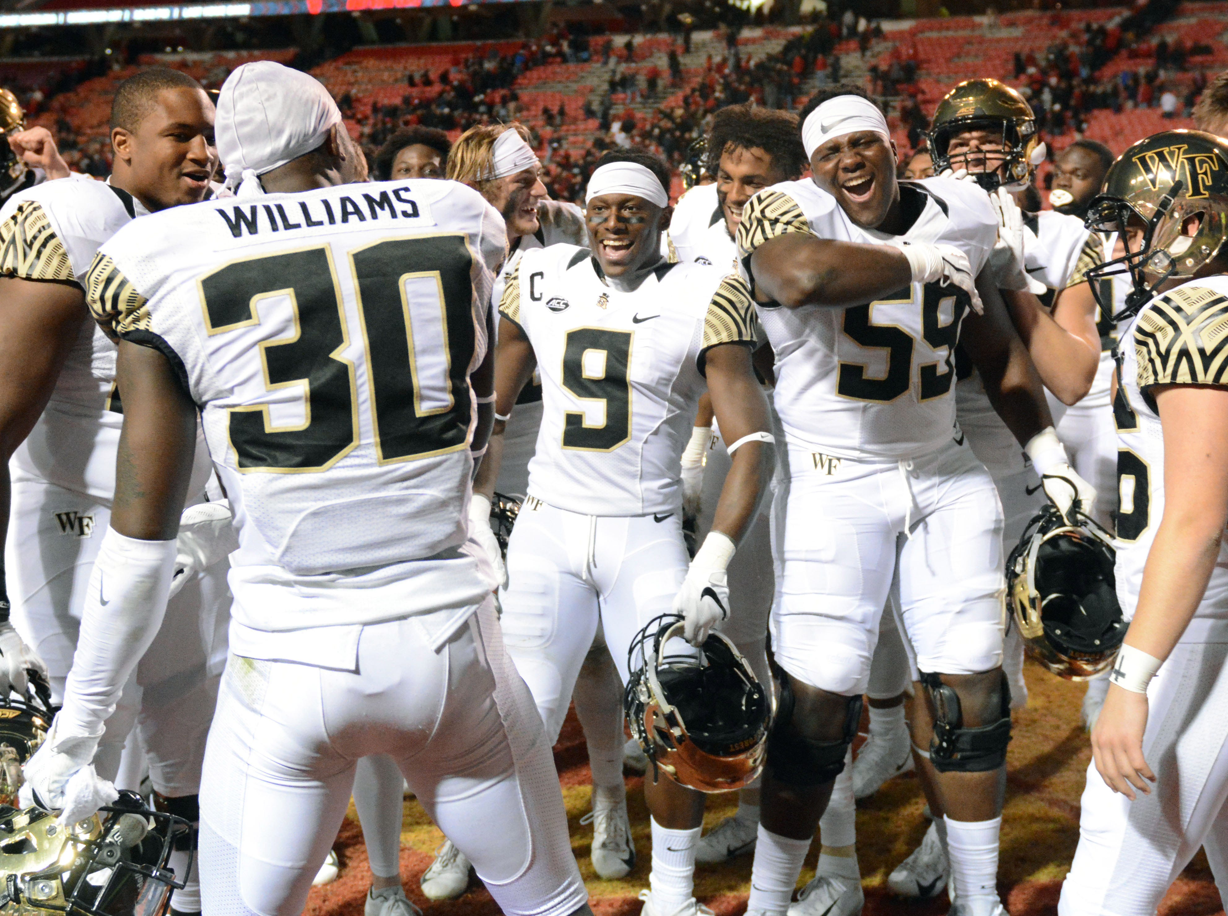 Wake Forest Demon Deacons players celebrate after beating the North Carolina State Wolfpack at Carter-Finley Stadium.