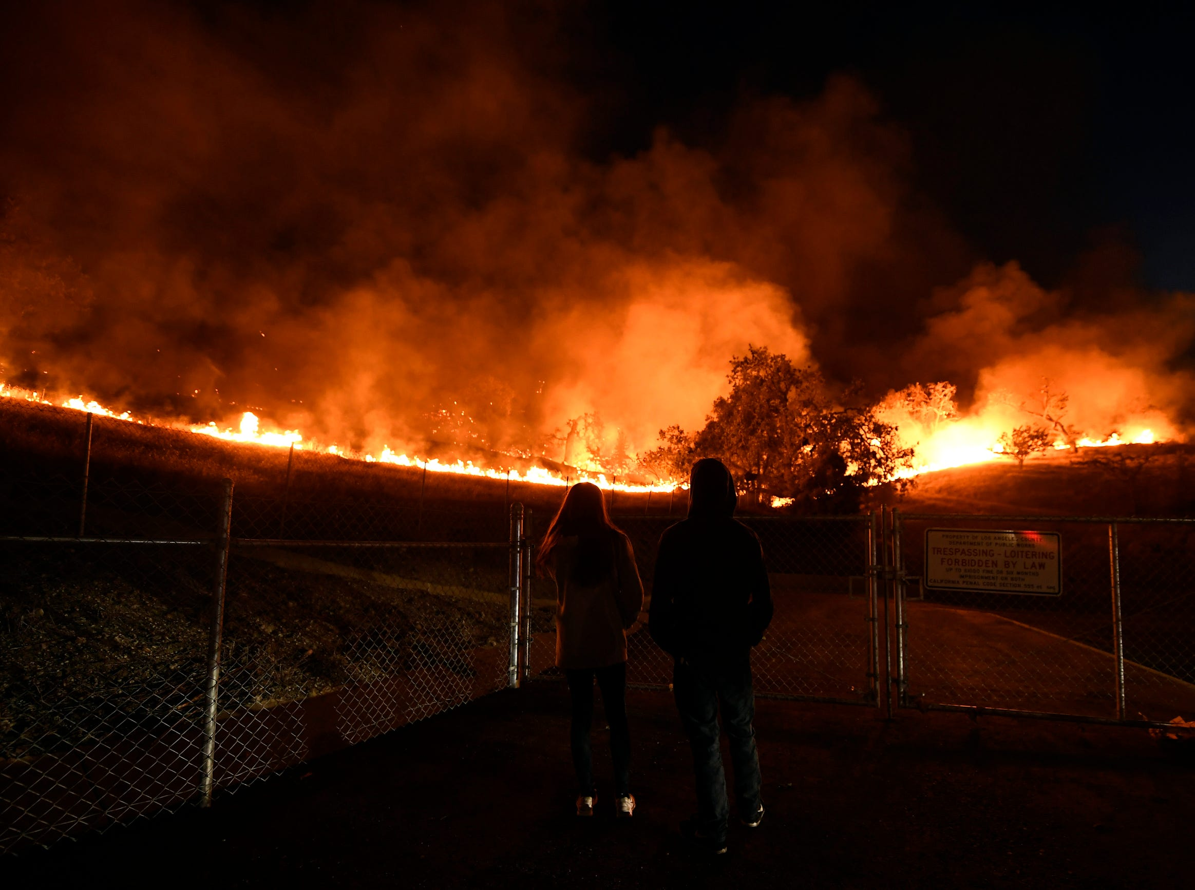 Residents take a look at the Woolsey Fire burning brush and trees in Agoura Hills, Calif. About 75,000 homes have been evacuated in Los Angeles and Ventura counties due to two fires in the region.