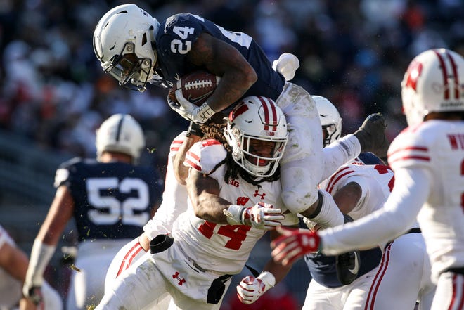 Penn State Nittany Lions running back Miles Sanders (24) leaps over Wisconsin Badgers safety D'Cota Dixon (14) during the fourth quarter at Beaver Stadium.