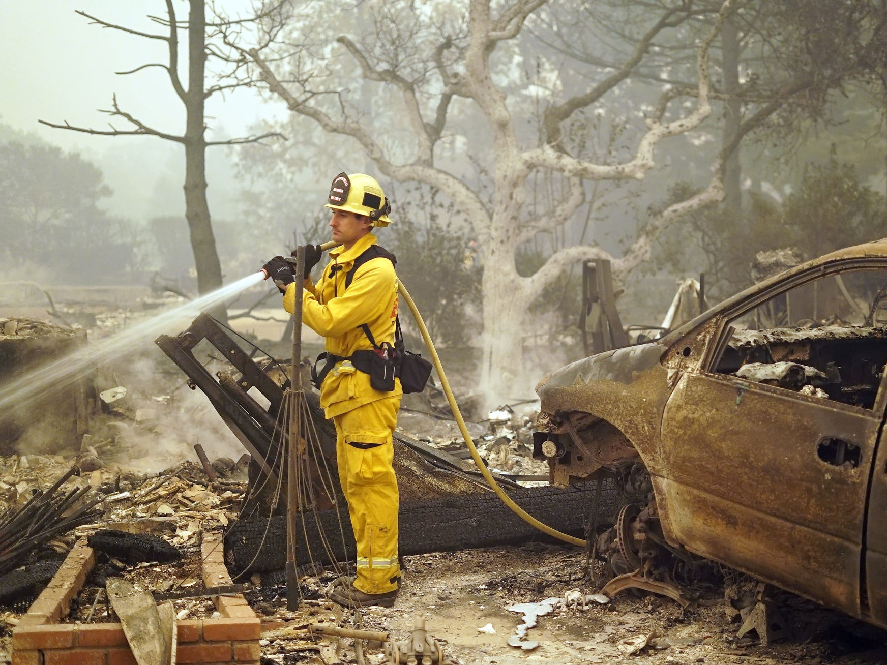Bakersfield, California-based firefighter Marc Eyherebide, 33, sprays down a destroyed home with water to prevent it from sparking any more fires in Paradise, Calif., following the Camp Fire devastation on Nov. 9, 2018.