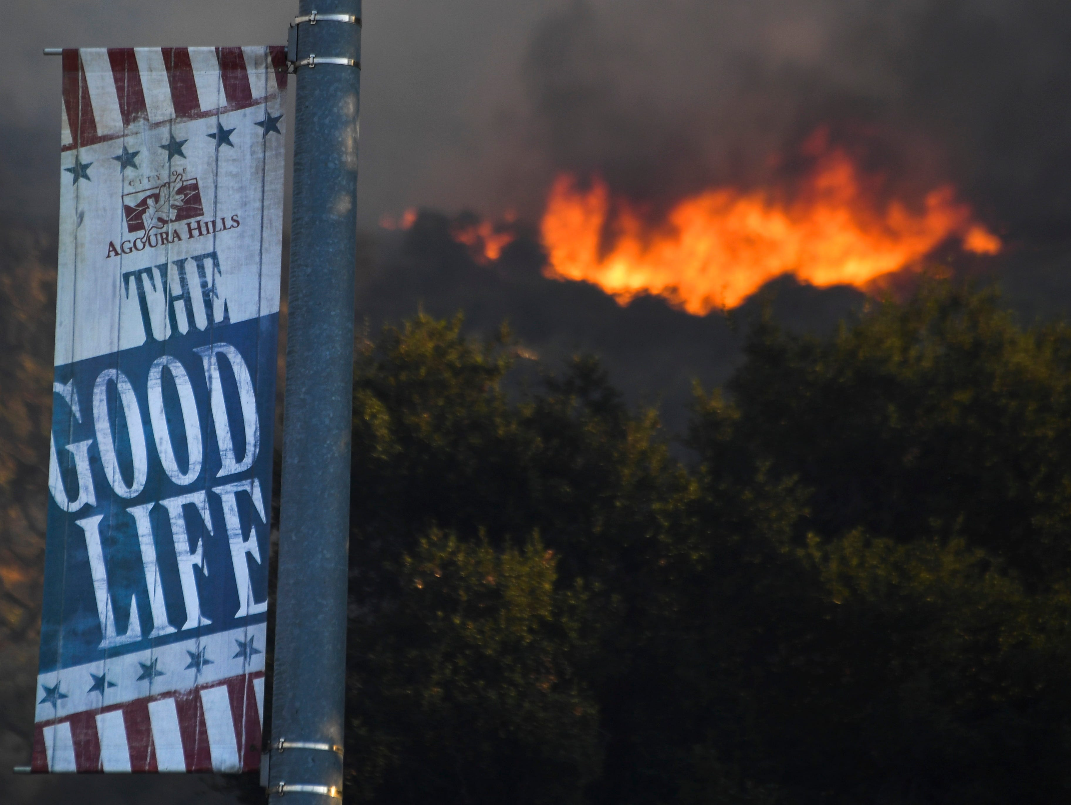 Flames send smoke into an Agoura Hills neighborhood in California on Nov. 9, 2018. The Woosley Fire in Ventura County has grown to over 35,000 acres and forced the evacuation of many residents.