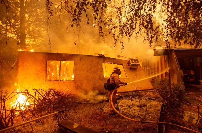 Firefighters battle flames at a burning apartment complex in Paradise, north of Sacramento, Calif. on Nov. 09, 2018. A rapidly spreading, late-season wildfire in northern California has burned 20,000 acres of land and prompted authorities to issue evacuation orders for thousands of people. As many as 1000 homes, a hospital, a Safeway store and scores of other structures have burned in the area as the Camp fire tore through the region.