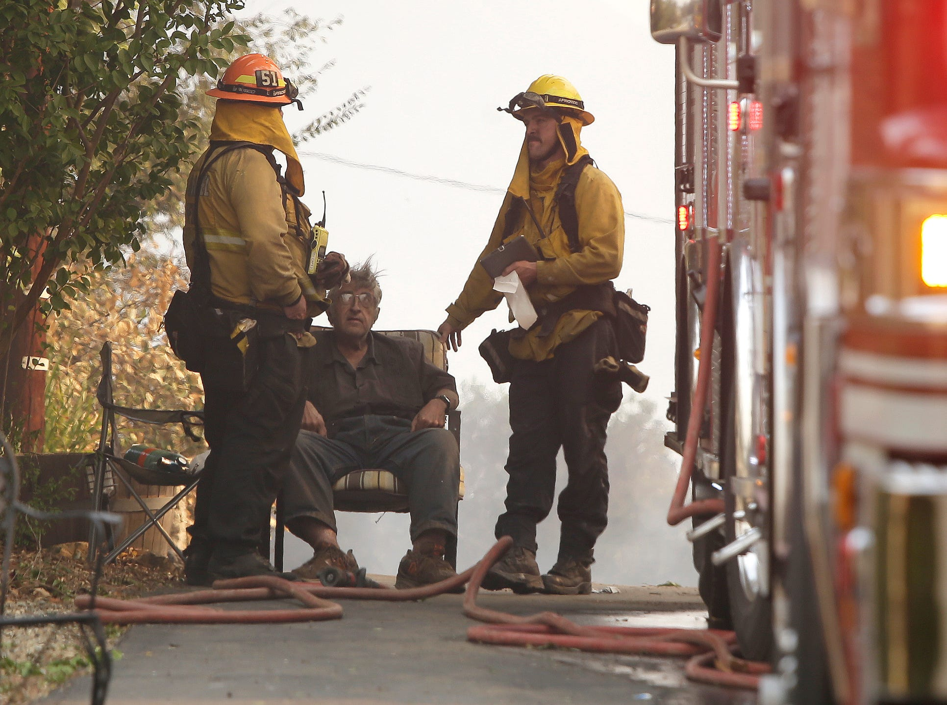 A homeowner who was overcome by smoke is attended to by firefighters as the Woolsey Fire swept through the Malibu Lake community.  The Woolsey Fire has led to the evacuation order for 75,000 homes. Fires across California fueled by very dry conditions and warm strong Santa Ana winds have destroyed structures and caused fatalities.