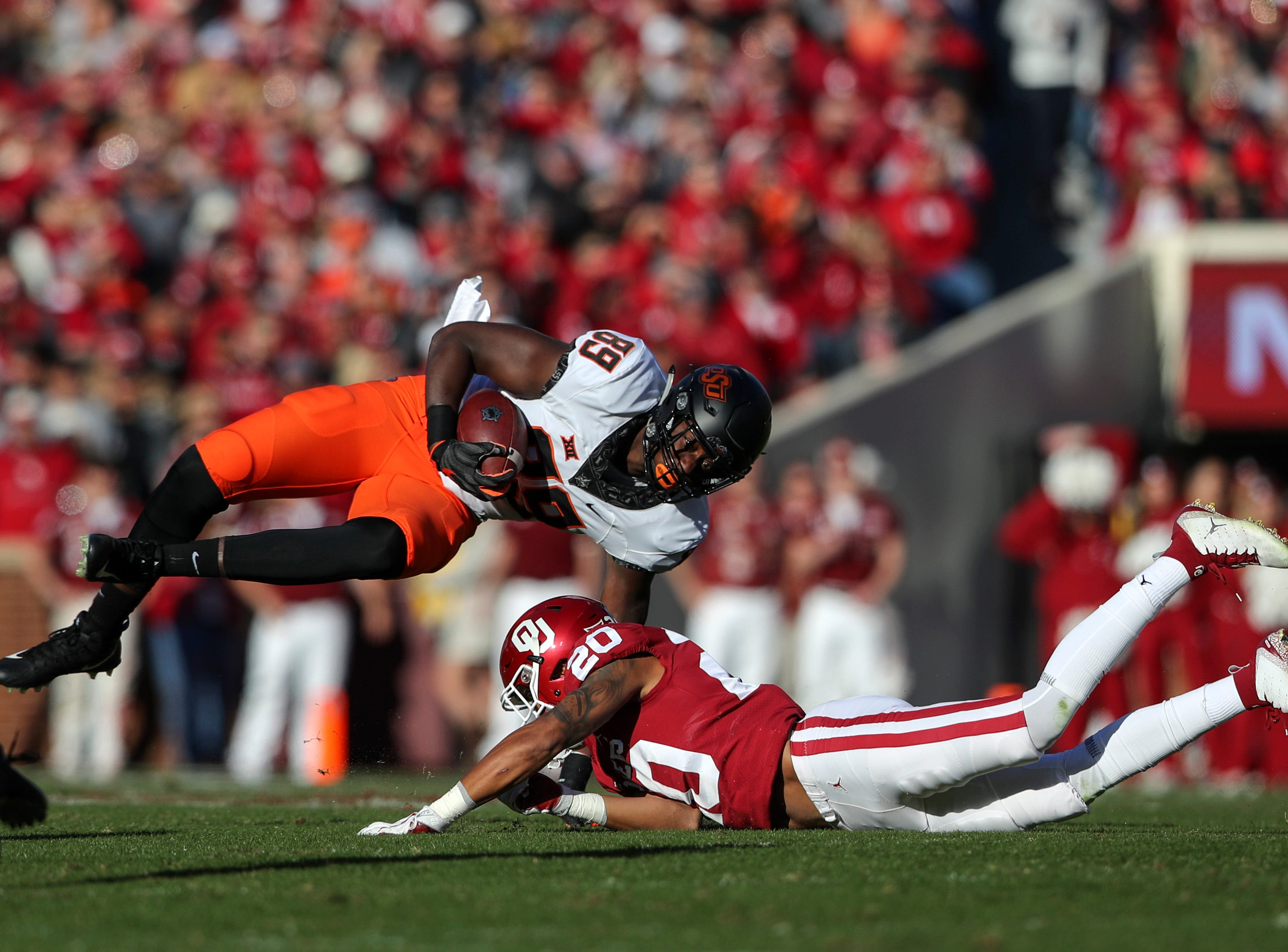 Oklahoma Sooners safety Robert Barnes (20) tackles Oklahoma State Cowboys wide receiver Jelani Woods (89) during the first half at Gaylord Family-Oklahoma Memorial Stadium.