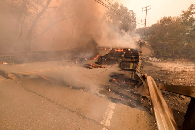The Woolsey fire burns the bridge on Mulholland Highway near Kanan Road in Malibu, Calif., on Nov. 9, 2018.