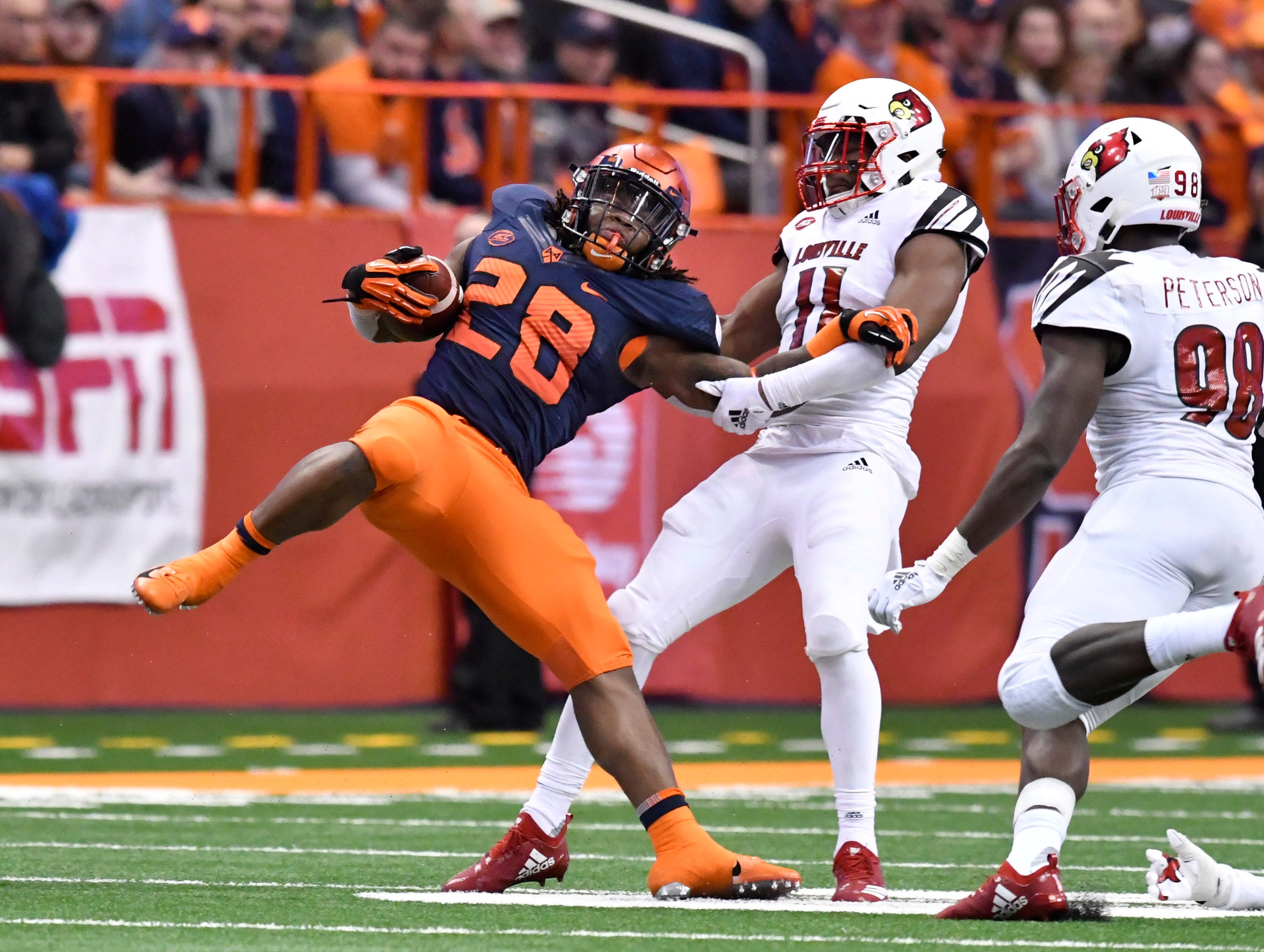 Syracuse Orange running back Jarveon Howard (28) is tackled by Louisville Cardinals safety Dee Smith (11) during the third quarter at the Carrier Dome.